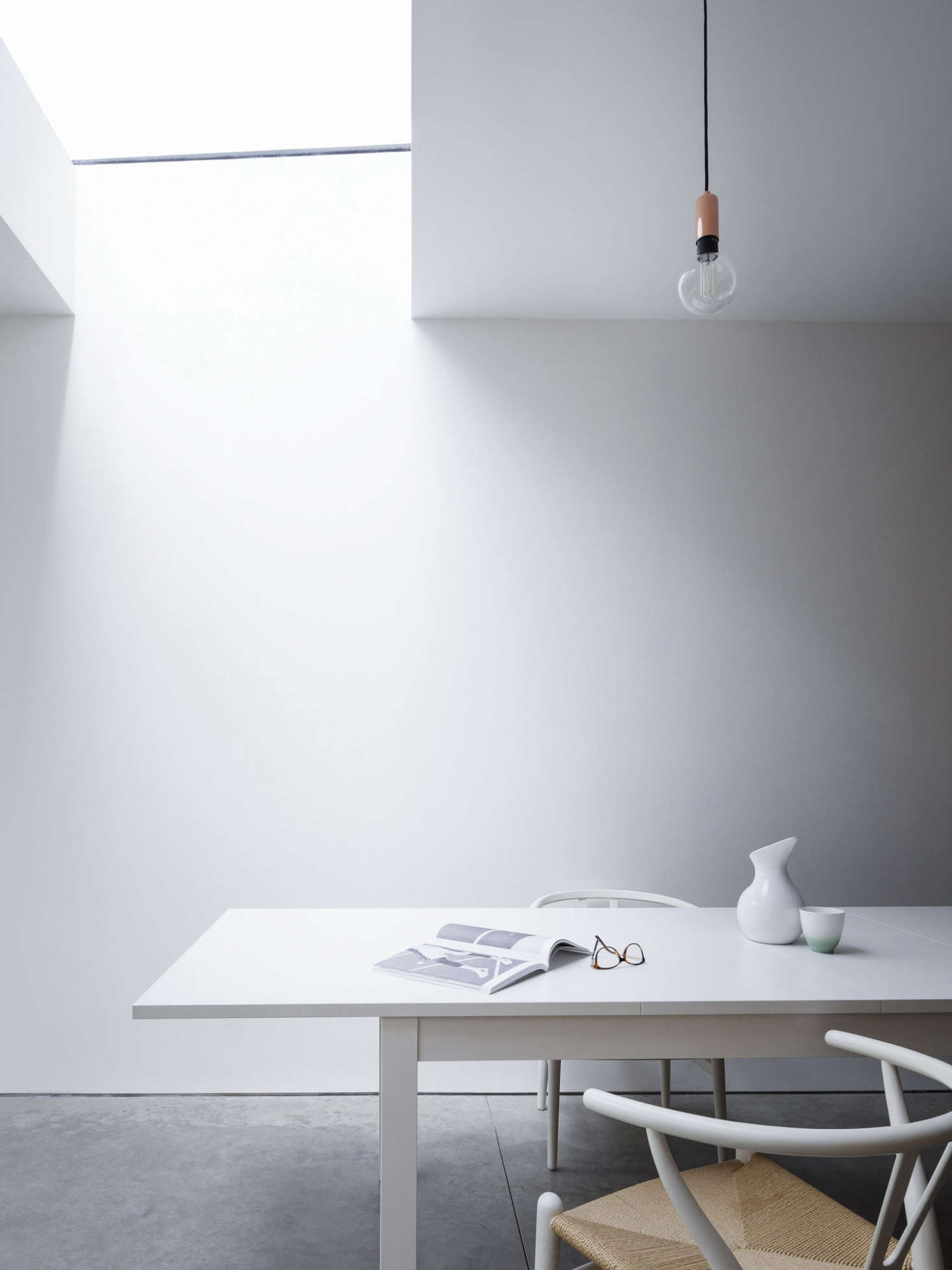 A large skylight floods the main room with natural light. Hans Wegner Wishbone Chairs surround an Ikea dining table. (For something similar, consider painting Ikea&#8