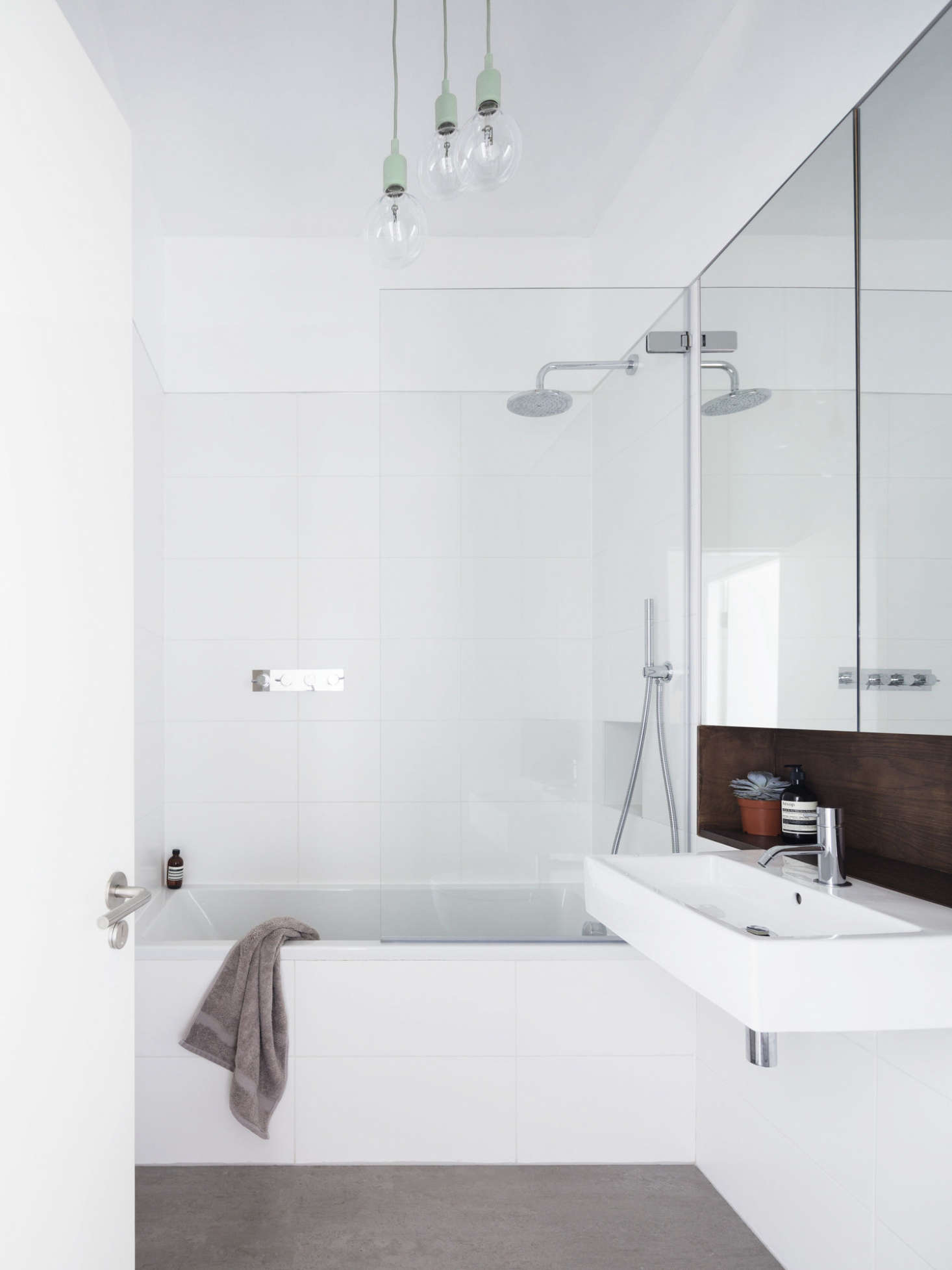 In the family bath, Johnston offset white tiles with a stone floor (Fired Earth&#8
