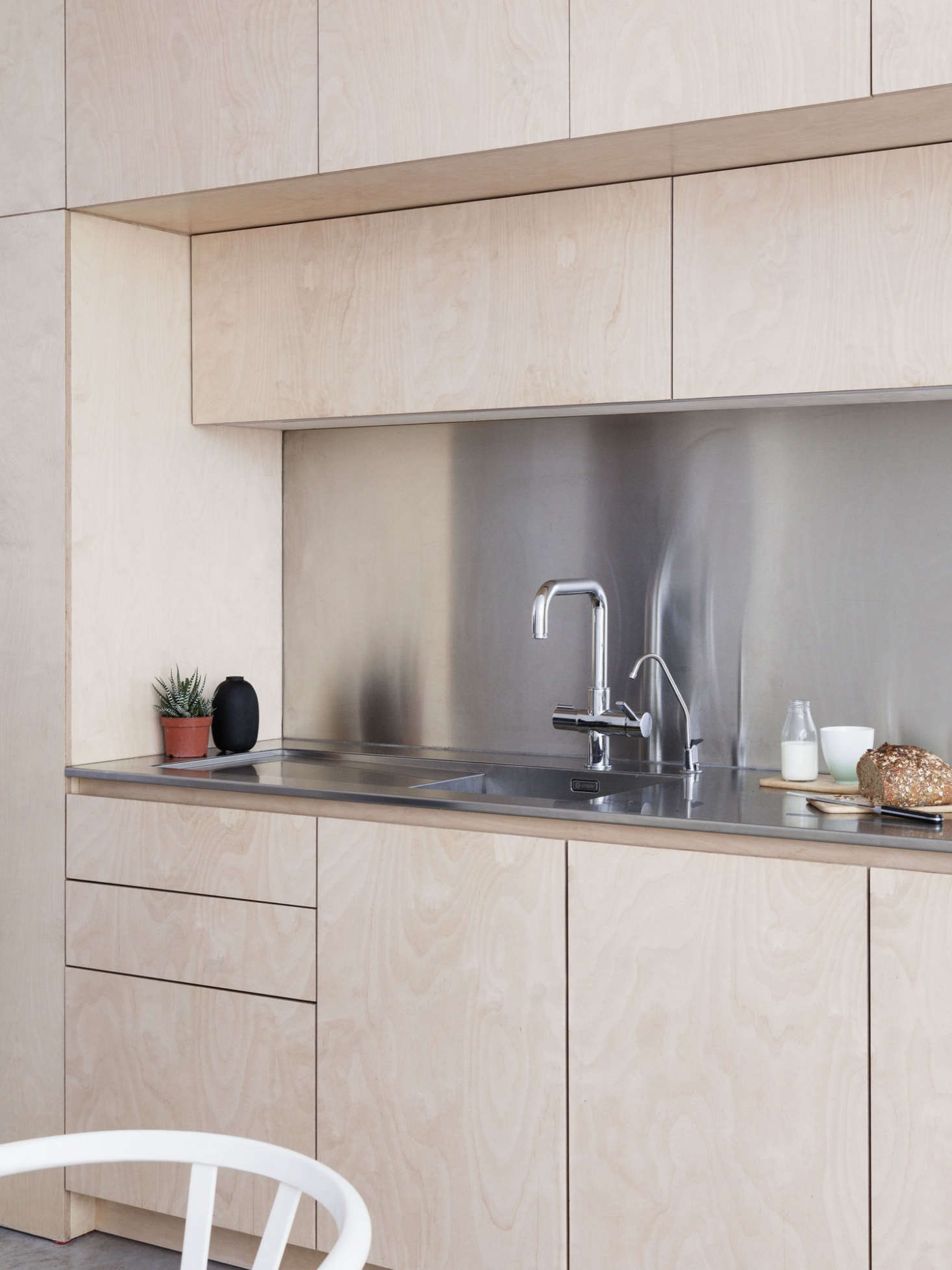 A Caple Cubit 0 stainless steel sink with drainer is set within the slim stainless steel counter. The faucet is Franke&#8