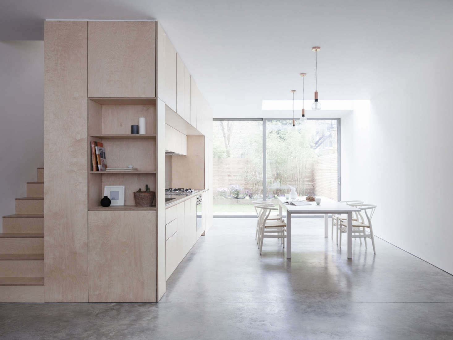 Larissa Johnston Architects designed a kitchen in a plywood frame (left) across from a large dining table surrounded by Wishbone Chairs from A London Townhouse Designed to Catch the Light.
