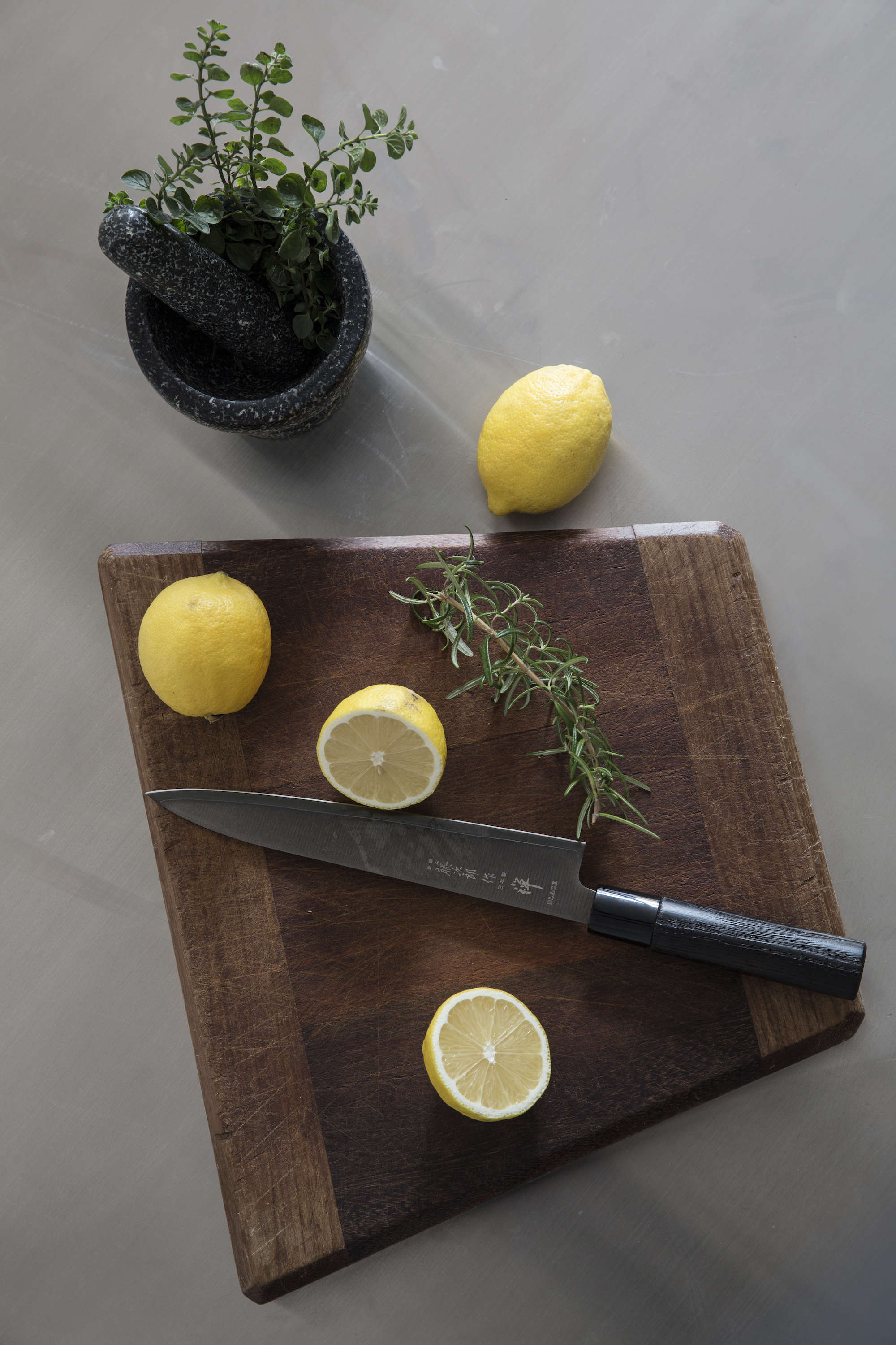dark-wood-cutting-board-with-knife-lemons-stainless-countertop