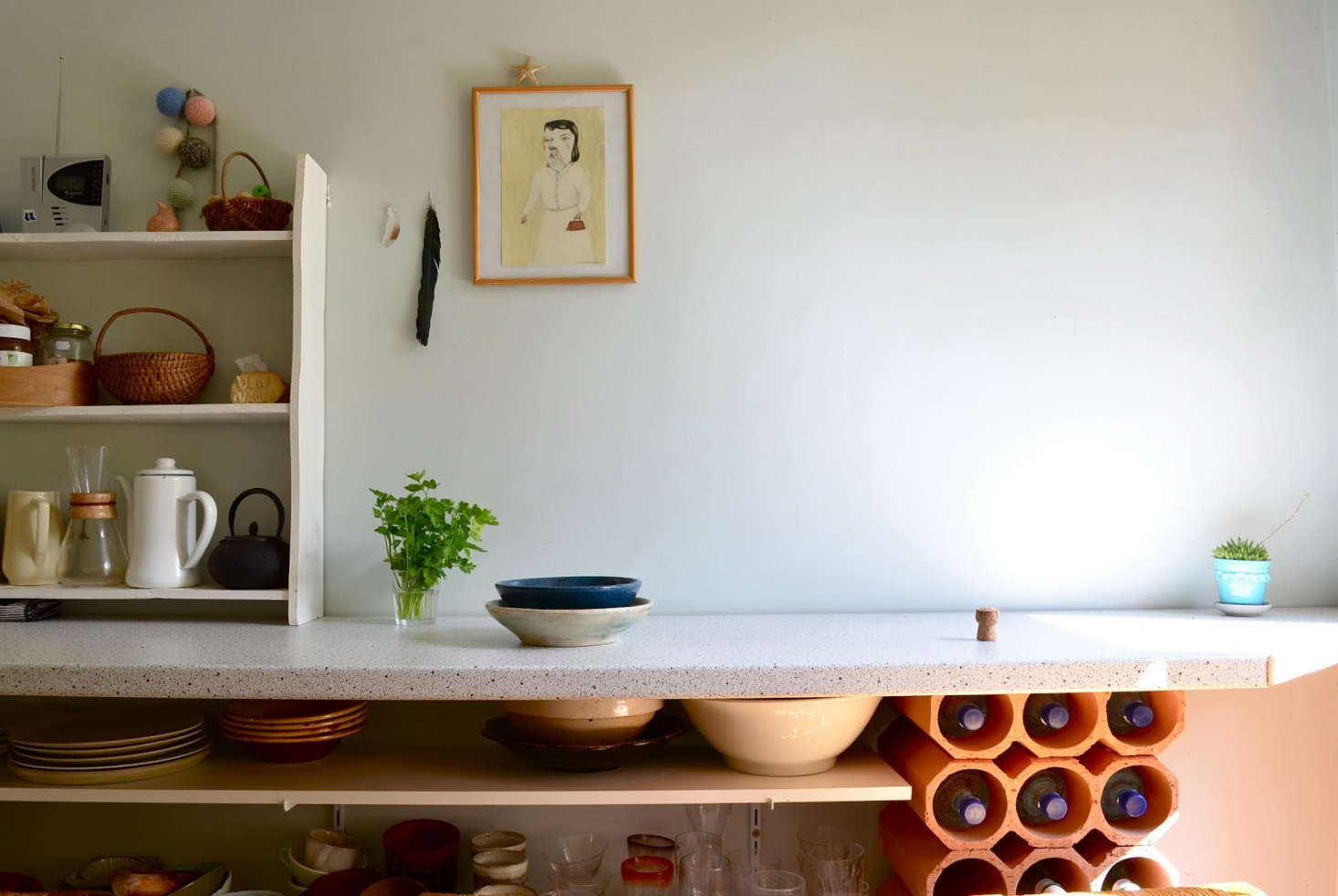 In Céret, a small village in the Pyrénées, the subtle kitchen of Japanese-born artist Masami Akatsuka, complete with a terracotta wine rack.