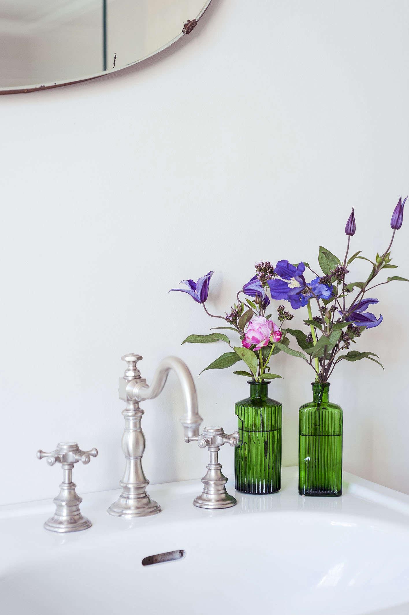 pedestal-sink-green-glass-bottles-flowers