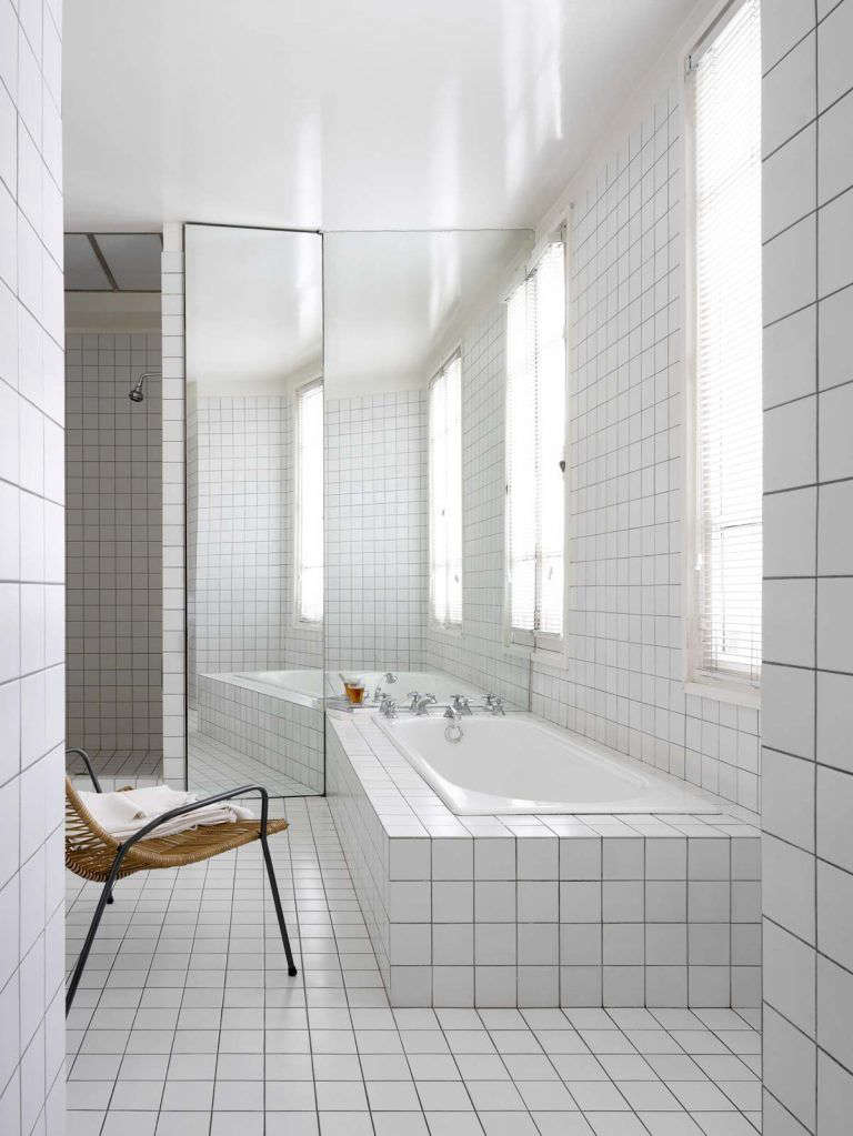 An artful built-in bath, surrounded in the same tile as the floor and walls, inA Minimalist Parisian Loft.Photograph fromRL Interior Architecture.