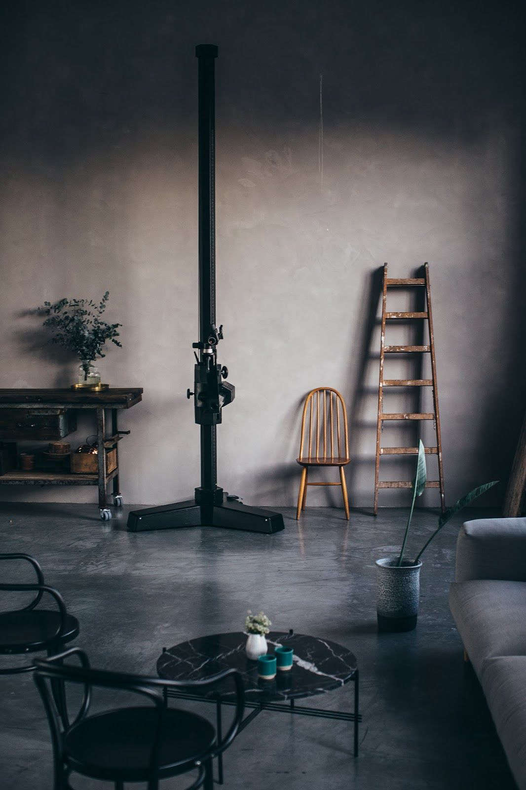 Alongside the kitchen stands Laura's towering tripod and a living area with a sofa and Black Marble Coffee Table, both by Gubi. Note that the island is on wheels for easy mobility.