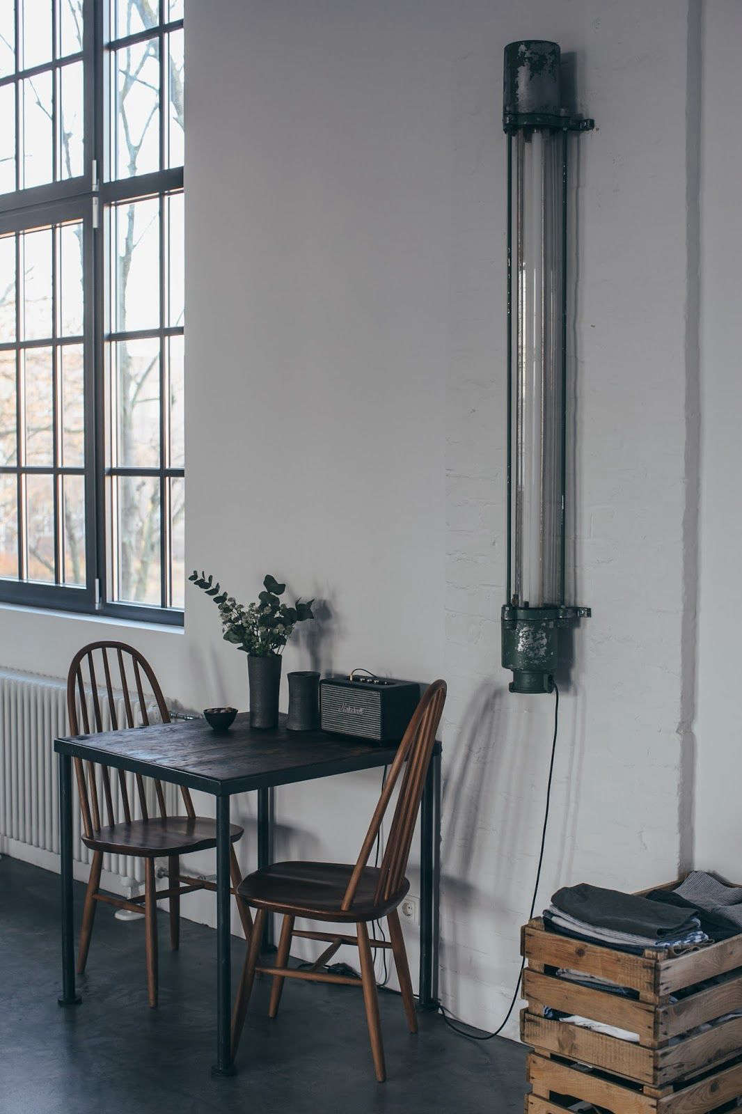 Above; A vintage factory light hangs next to a table for two with a pair of old Windsors.