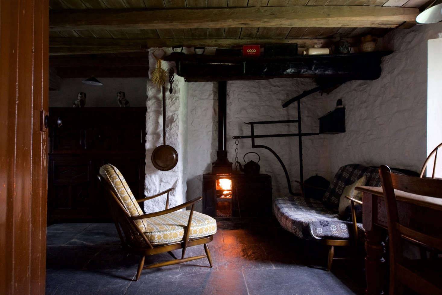 A wool blanket serves as makeshift slipcover in The Welsh House: Slow Living in a Traditional Cottage, Available for Rent, in Wales. Photograph by Will Venning for Remodelista.