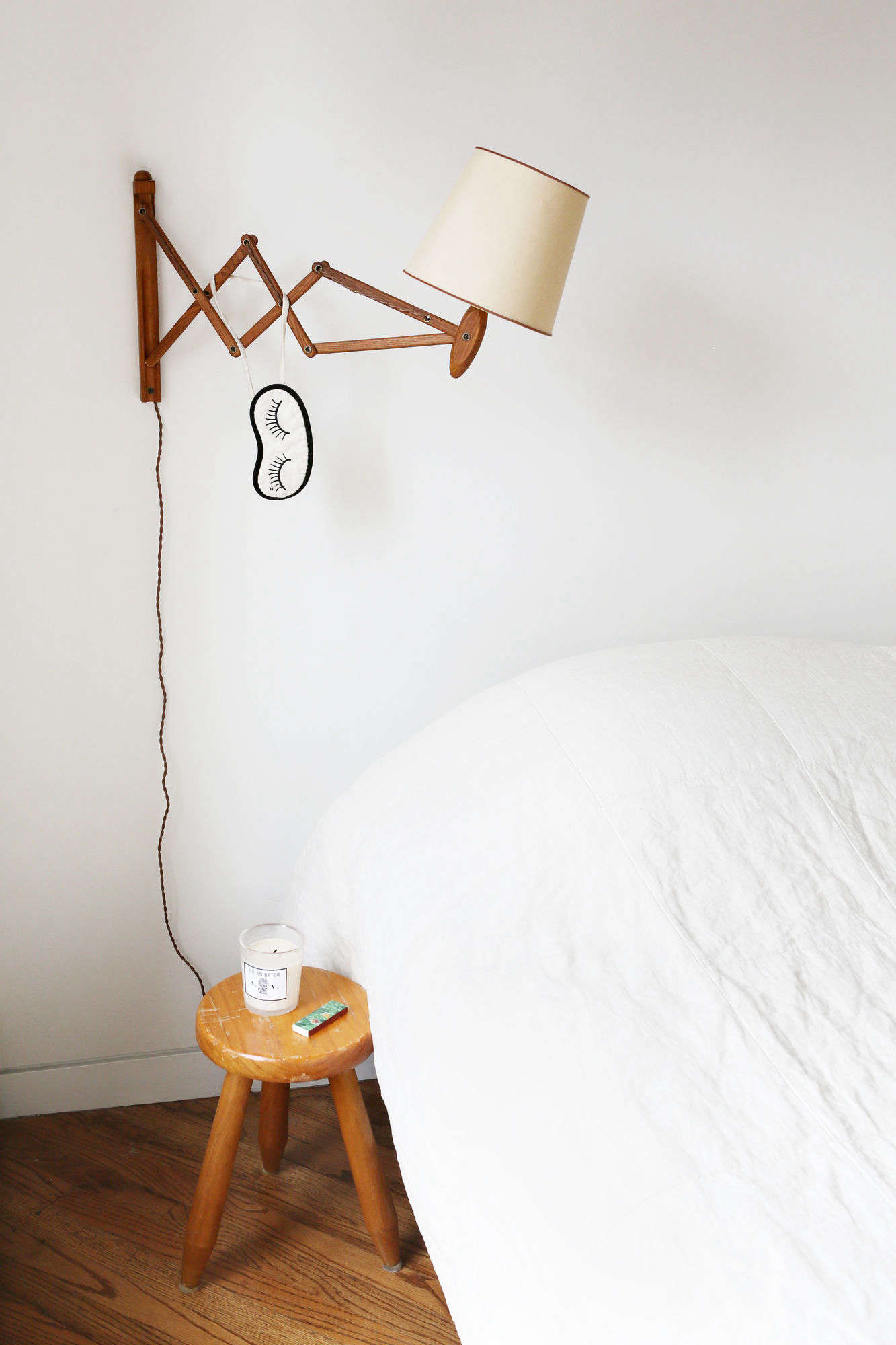 Javitch keeps a few wellness essentials by the bed: a candle and long matches. A sleep mask hangs from a vintage accordion wall lamp from Orange Furniture in LA.