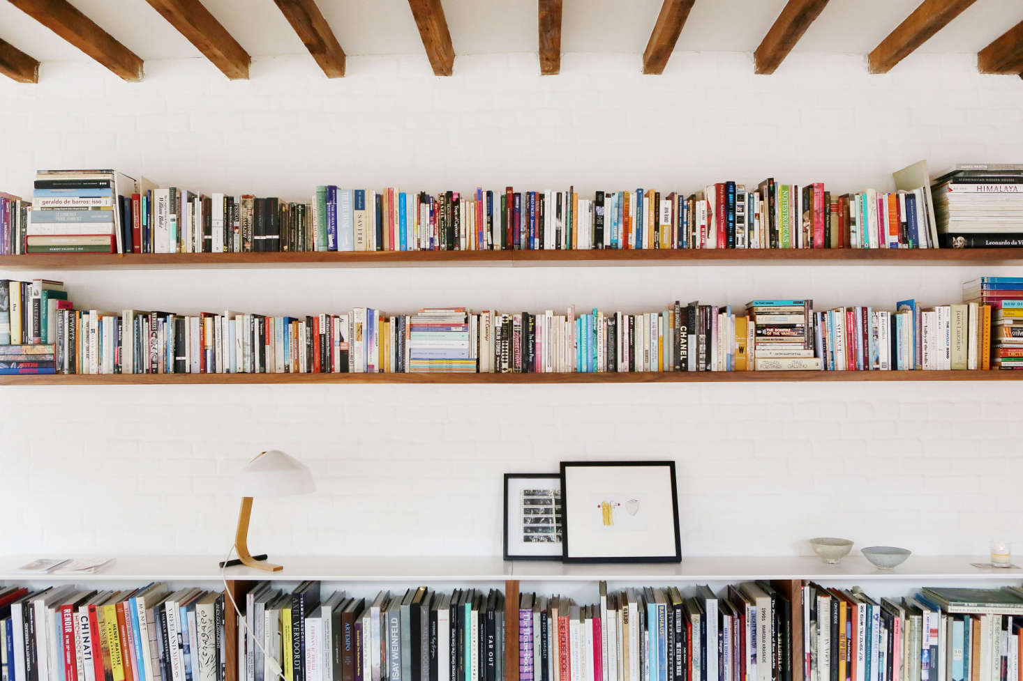 Built-in shelves replace freestanding bookshelves and create a display shelf for art and favorite objects. Long uninterrupted shelves feel expansive rather than cramped.