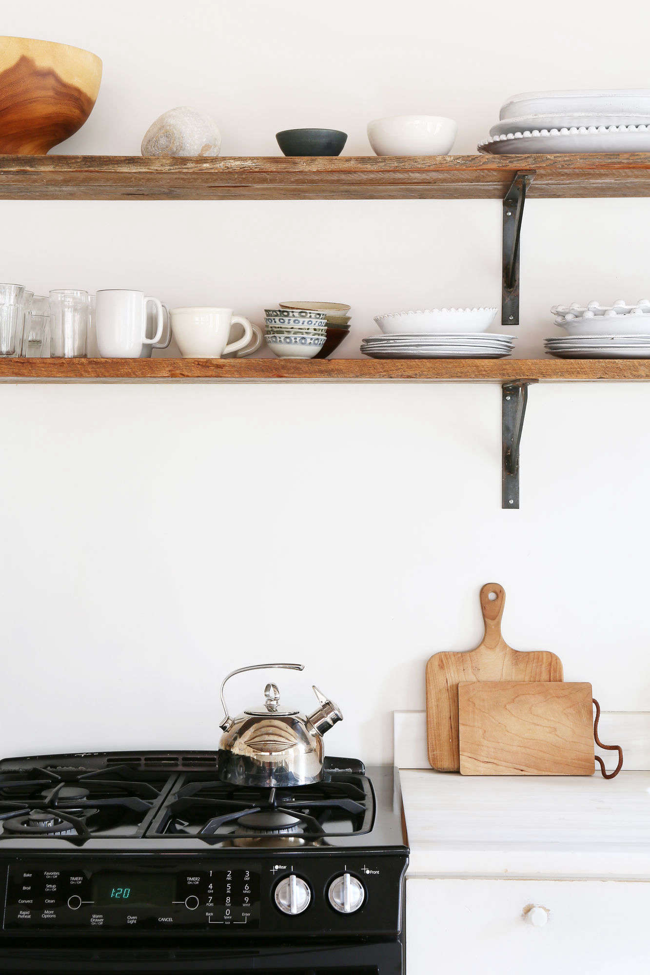 Open shelves in place of overhead cabinets make the small space feel open and display the couple&#8