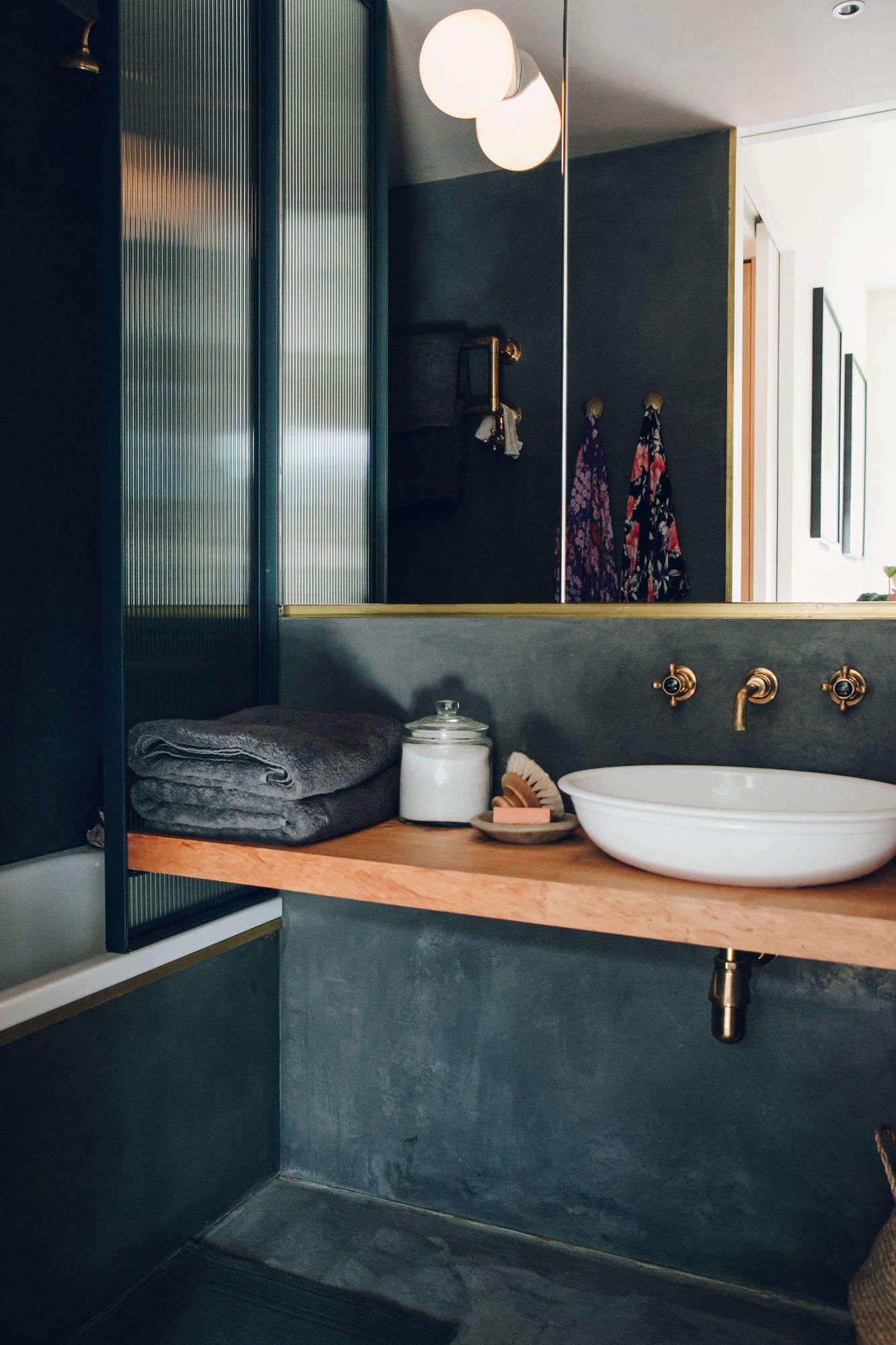 """The shower doorwas a custom design;it's fixed on oneend to support the custom countertop, made of a single piece of Monterey cypress wood. """"While coming upwith the materialpalette, we were drawn to thebeauty of combining dark gray tadelakt with the warm wood of thecountertop, finished off with brass detailing."""""""