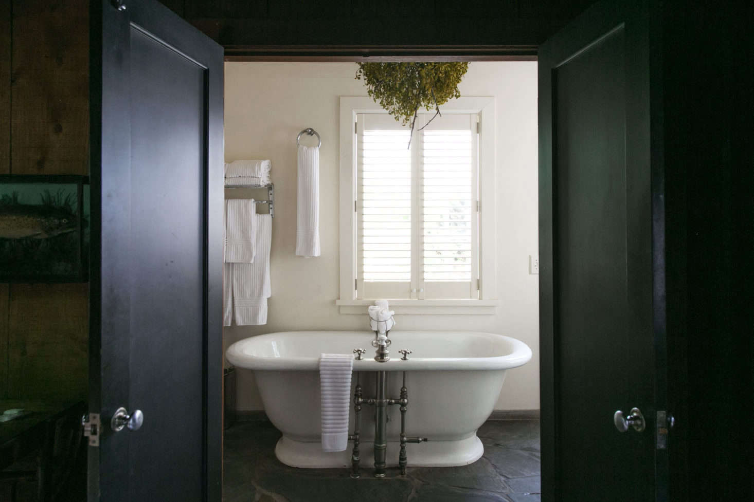 The White Bath Has A Rough Hewn Stone Tiled Floor And Matte Black Painted  Doors