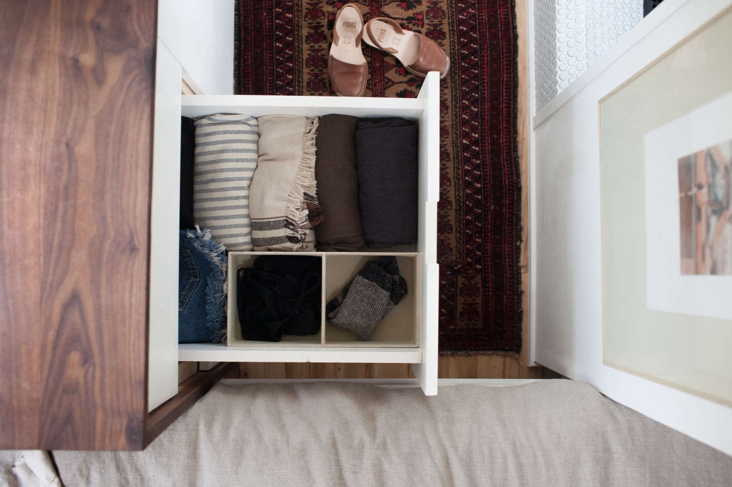 A Walnut Covered Built In Dresser Provides Compact Storage For Clothing  (folded,