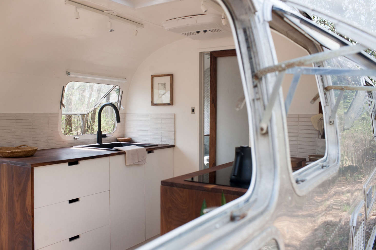 The Wood And Clean Lines Of Interior Contrast With Airstreams Sleek Silver Exterior