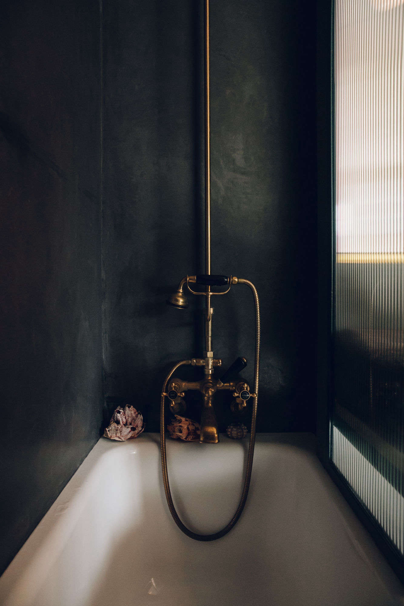 The shower tub fillermatches the sink's faucet, alsofromBarber Wilsons & Co.
