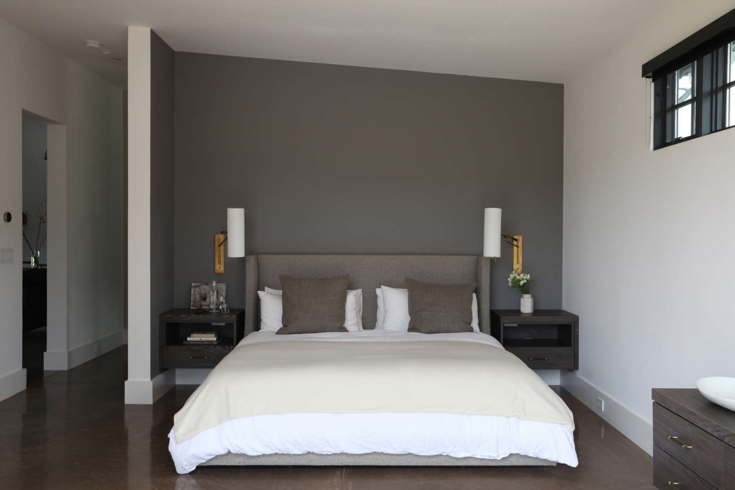 In the master bedroom, twoFrankfort Articulating Wall Lights from Circa Lighting flank afabric-backed bed from Room & Board. The nightstands are custom and the accent wall is painted in Farrow & Ball Mole&#8