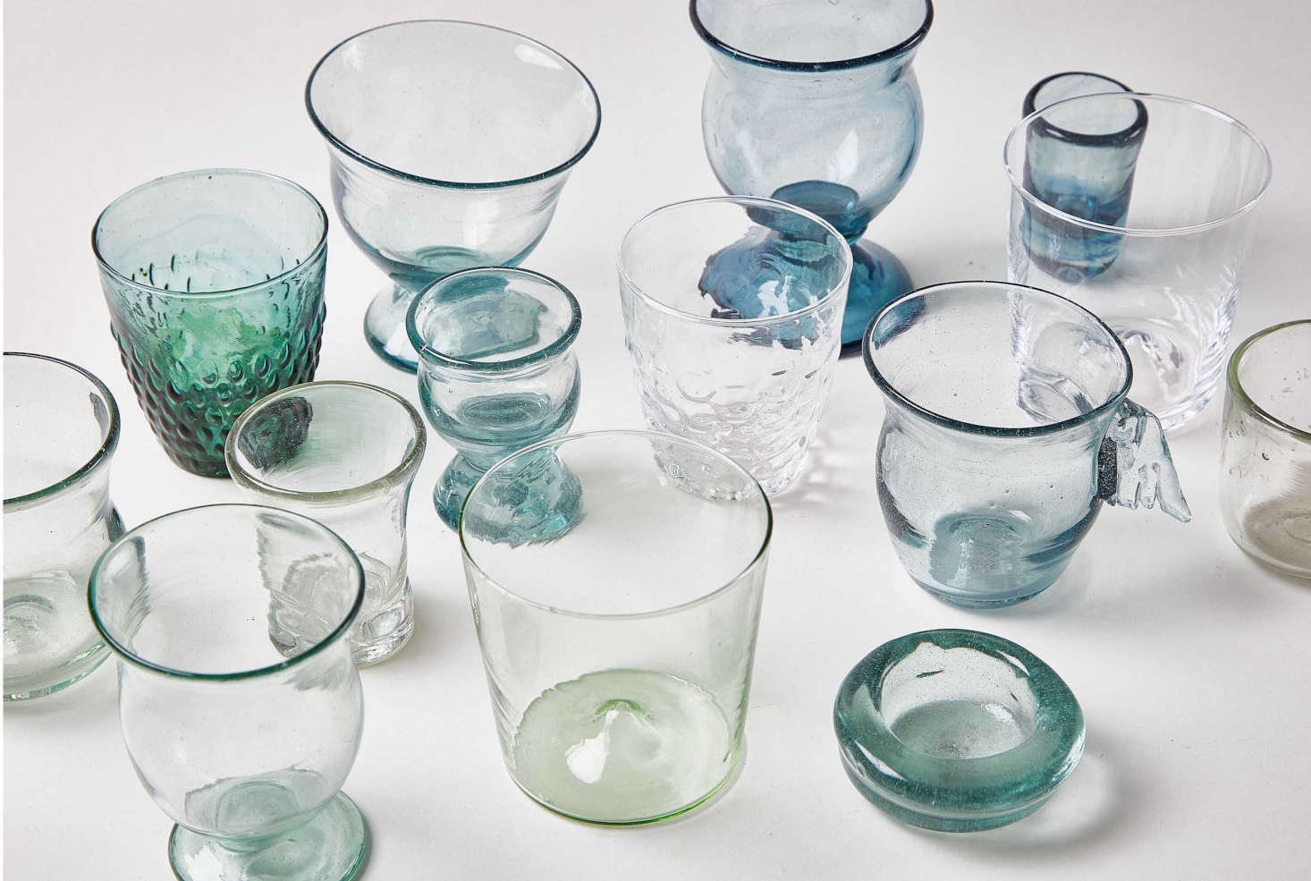A collection oftumblers, including the La Riccia Footed Drinking Glass, free-blown from recycled glass by an artisan in the Maremma countryside; $65 each.