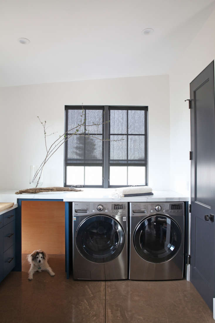 above dark gray roller blinds paired with dark gray window frames in a laundry room featured in in california wine country a modern farmhouse for a brit