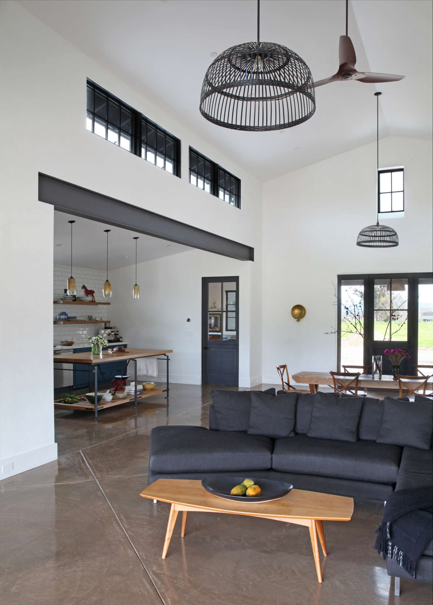 The two black basketweave pendant lights above the living and dining are from Ikea, modified with the power cord installed inside a down rod to minimize movement. The coffee table is from Room & Board.