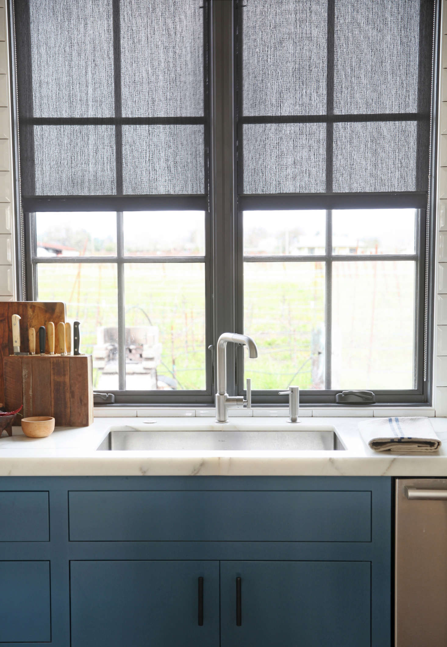 The kitchen window overlooks a view of the environs; landscaping is still in progress. The faucet is by Kohler, the sink is from Kräus, and the countertops are white Calacatta Oro marble.
