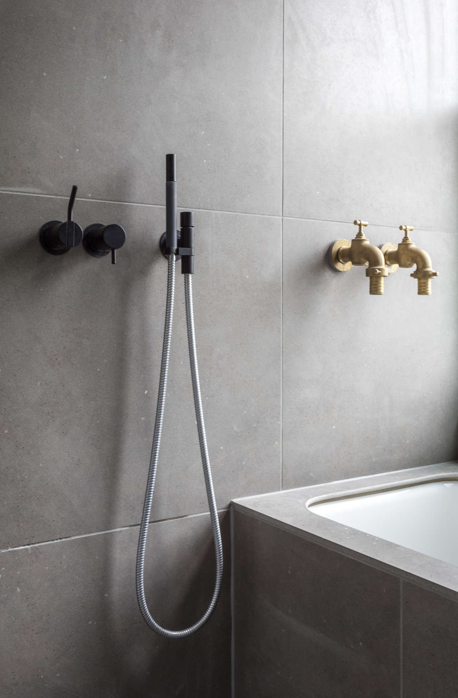"Refined meets rustic: the matte black Shower Mixers are from Vola and the brass bath taps are another score from a hardware store in Braga, Portugal: ""They're very one-off but high quality,"" says Astridge."