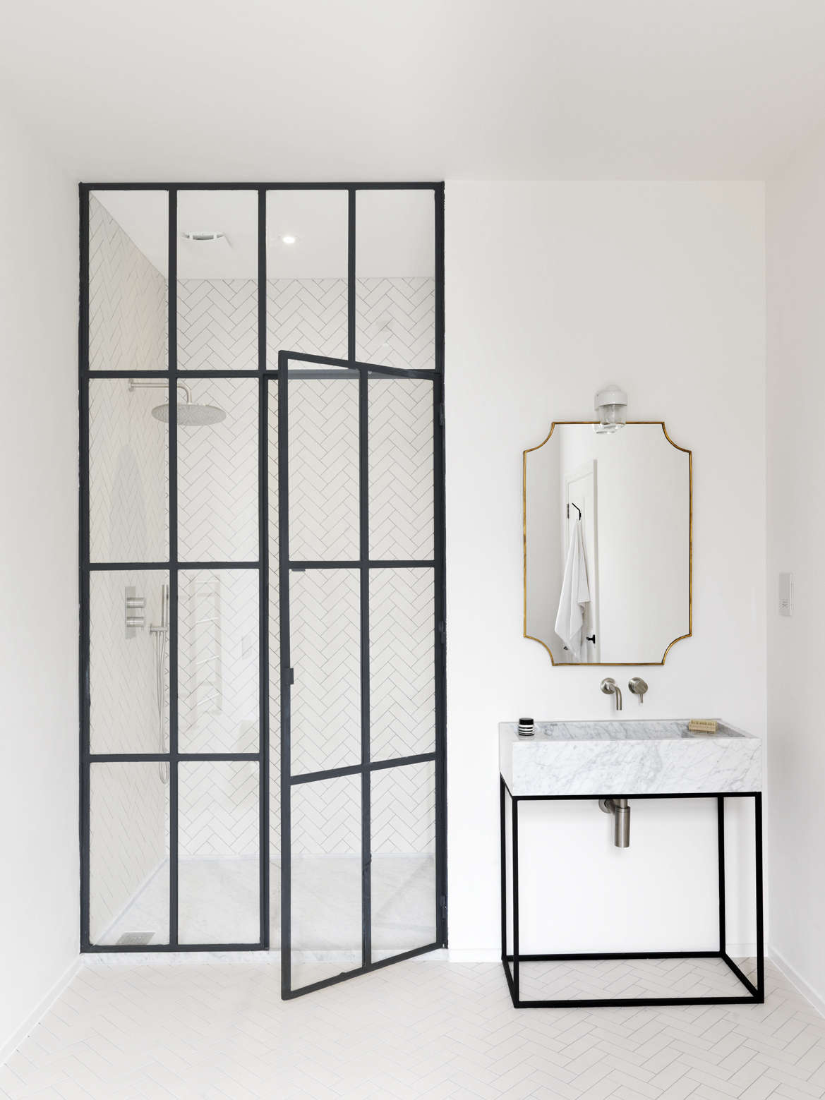 An interior steel frame door adds industrial structure to an all-white bathroom; see