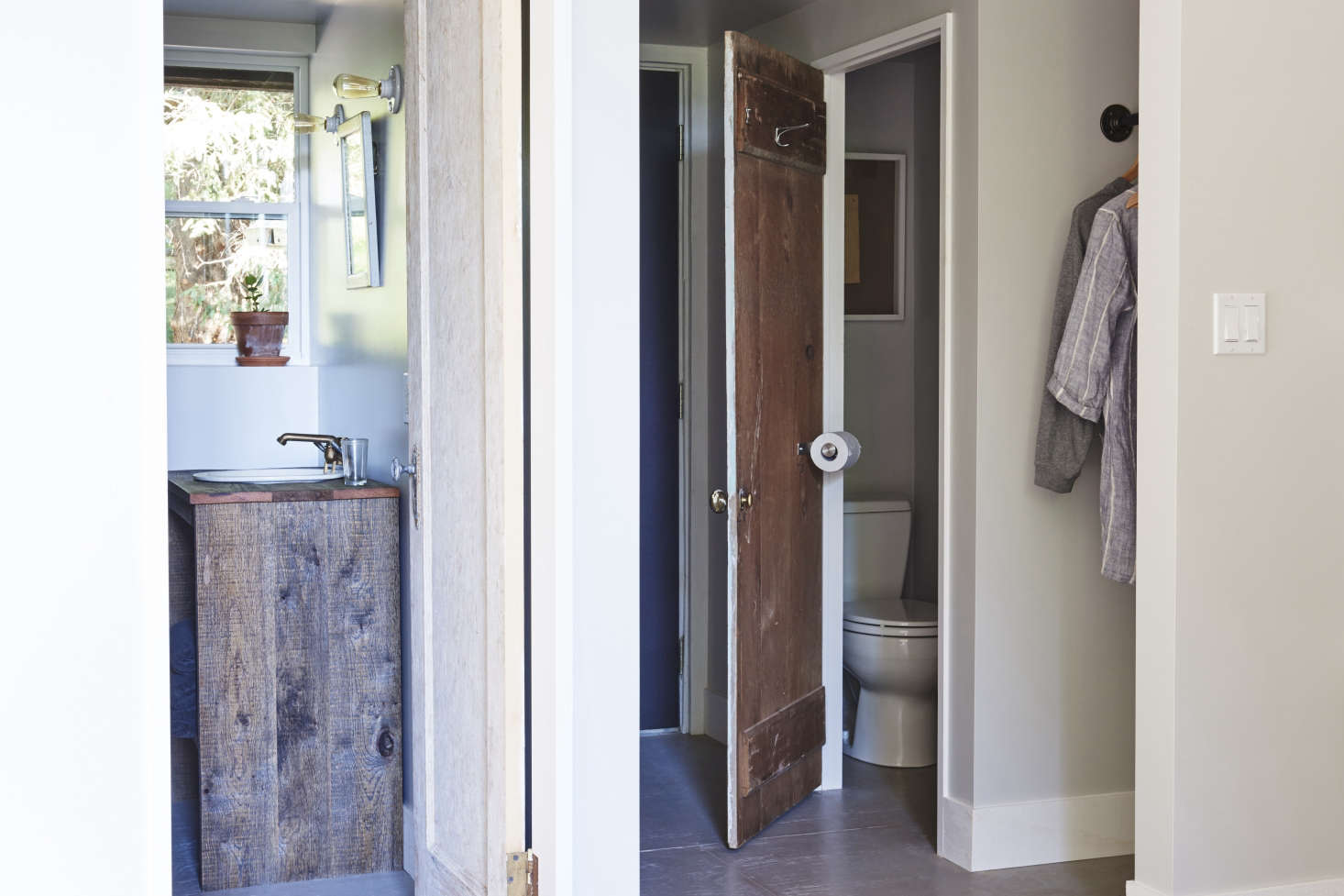 Thebathroom suite with a reclaimed-wood vanity. In the WC, a space-savinghack: a toilet-paperholderaffixed to the door.