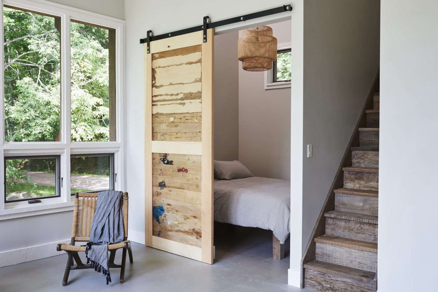 A sliding barn door is made of salvaged wood from the artist's cabinet drawers (paint splotches included).