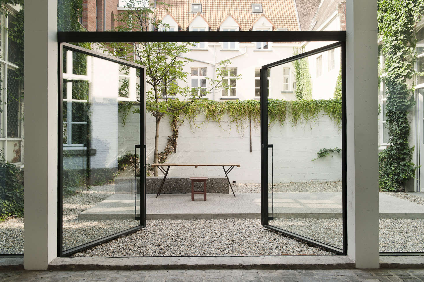 The gallery space leads onto a pebbled courtyard with a concrete island.