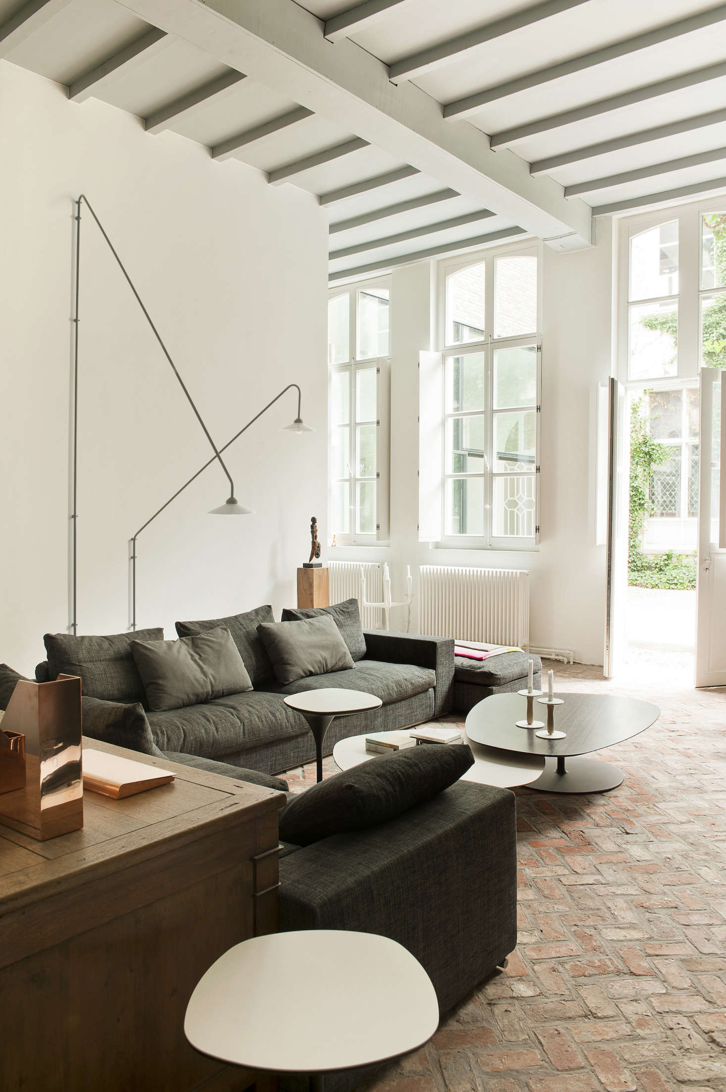 A Flexform Sofa and articulating wall lights by Muller Van Severen.