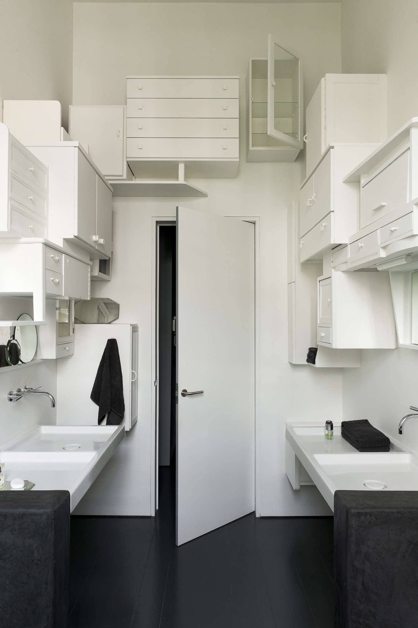 The bathroom features walls of white painted cabinets.