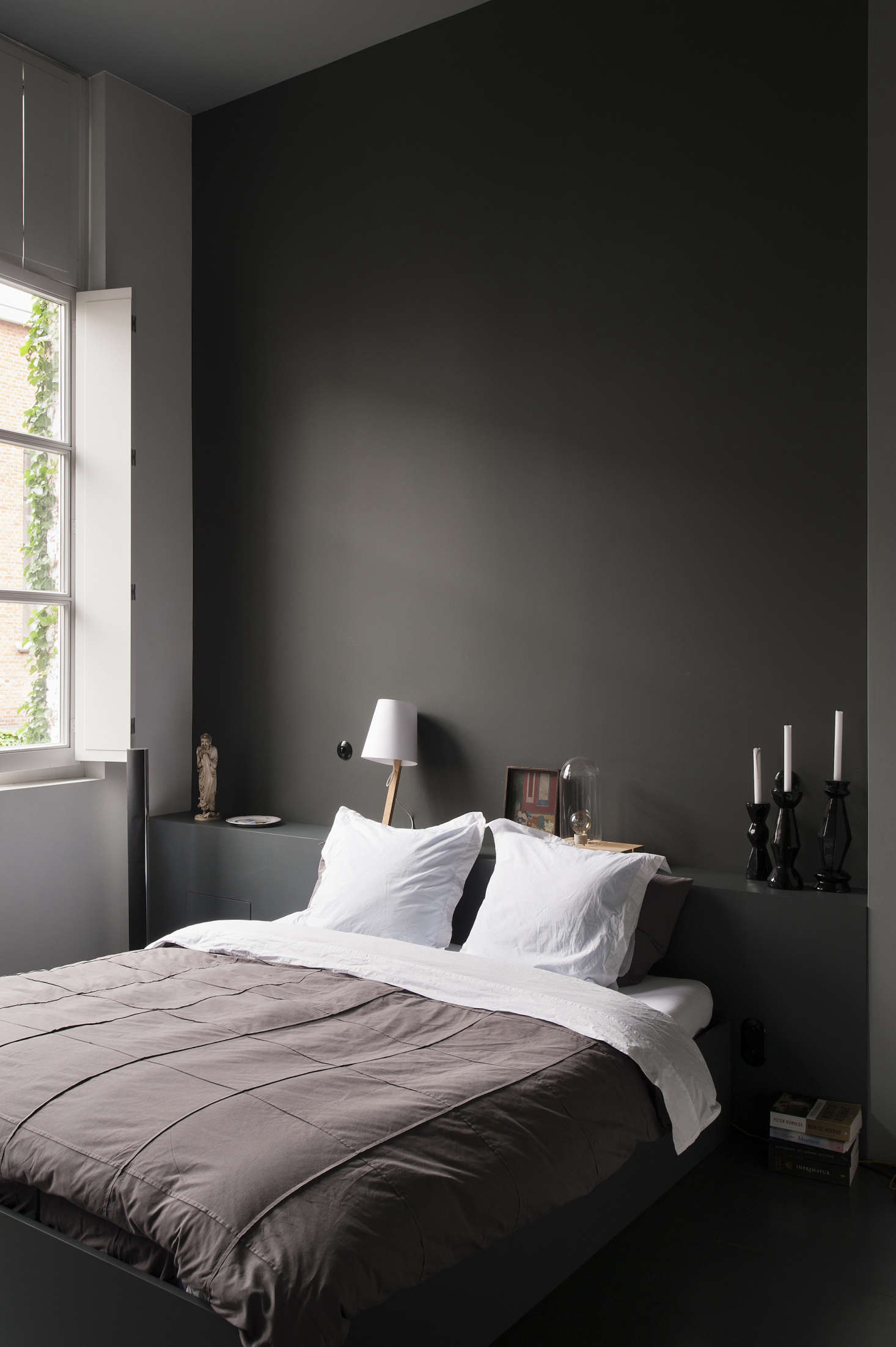 The bedroom with a darker palette than the rest of the bright white gallery-home space.