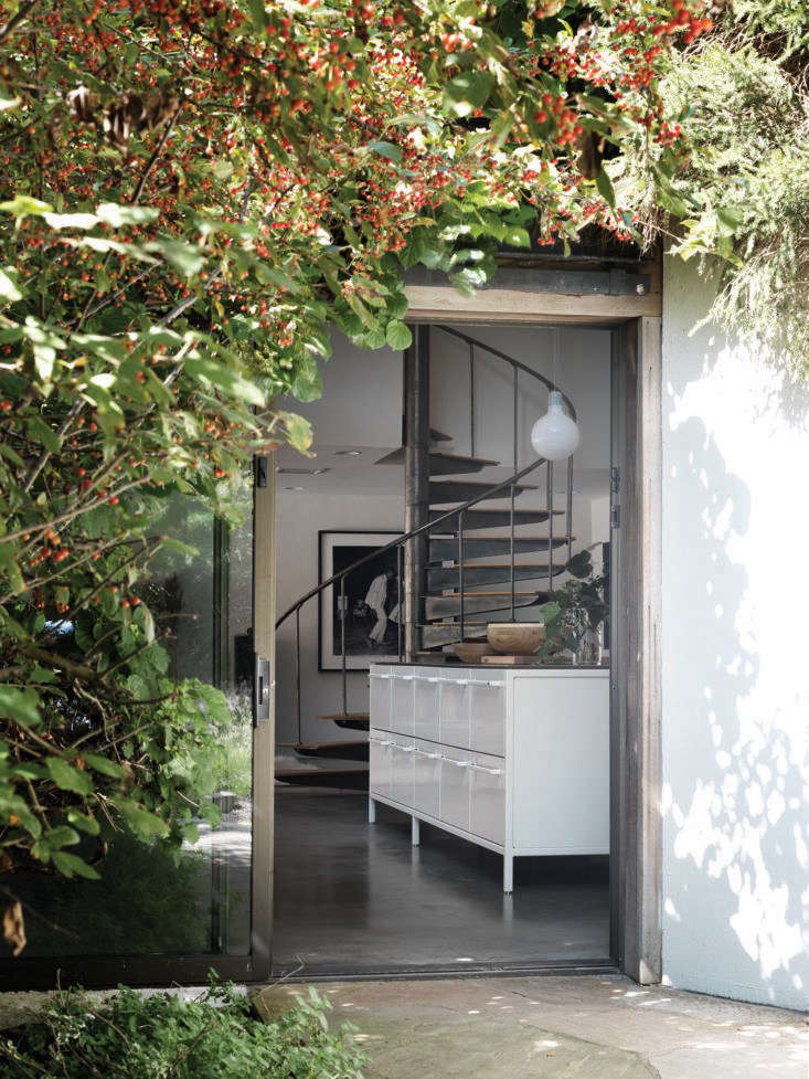 A foliage-framed sliding glass main entrance opens to an expansive kitchen-living room in a converted potato barn used as a country house.