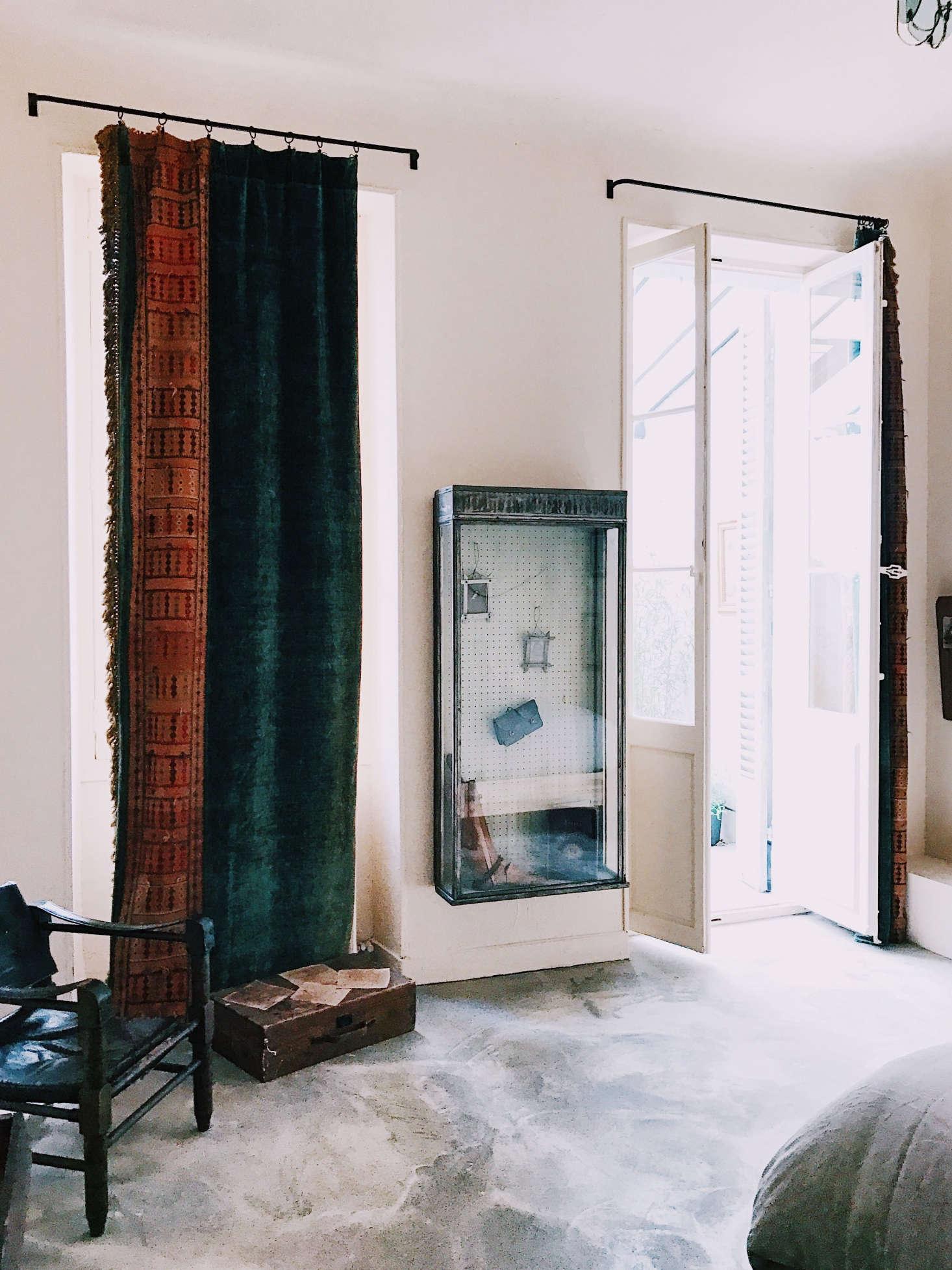 Antique textiles serve as window coverings.