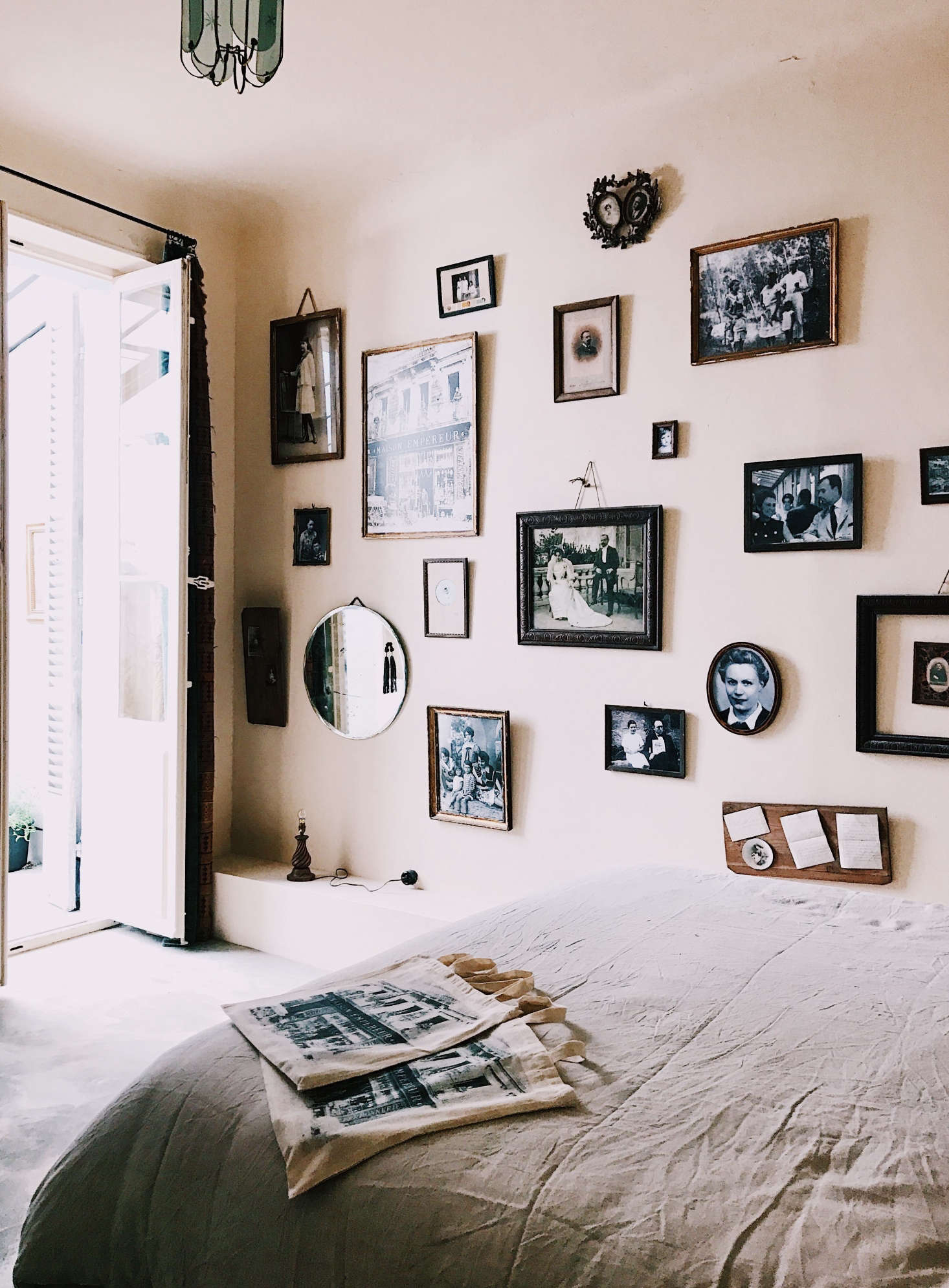 The bedroom has a gallery wall featuring framed historical photographs.