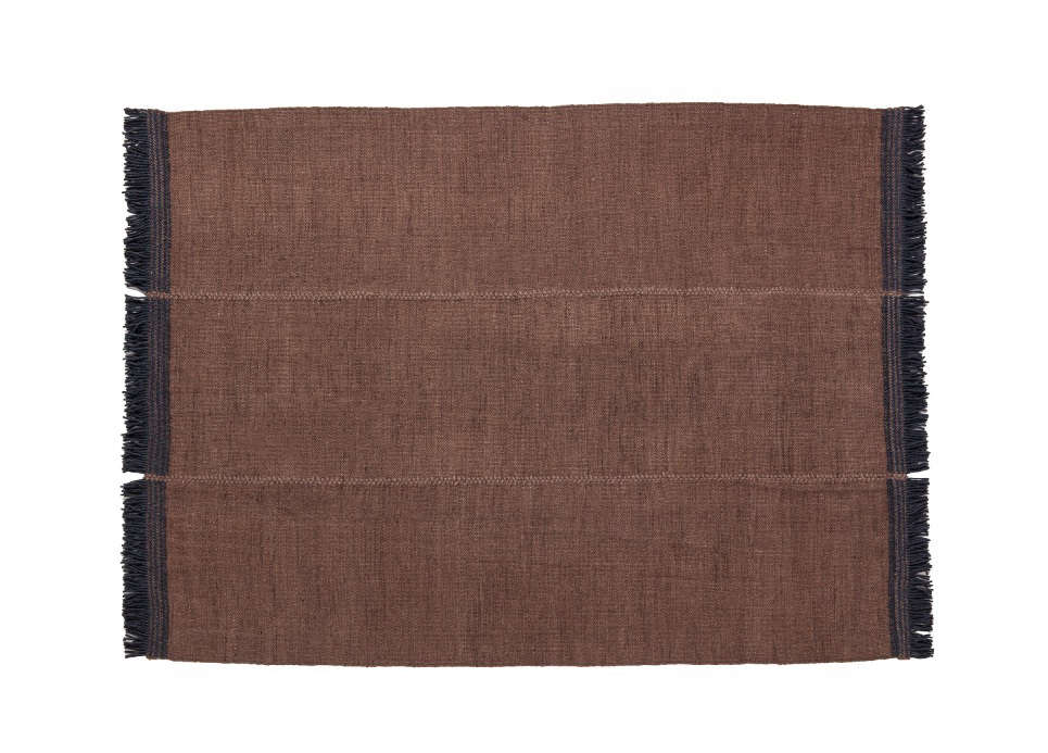 This Mía Brown rug has contrasting embroidered fringe in navy.