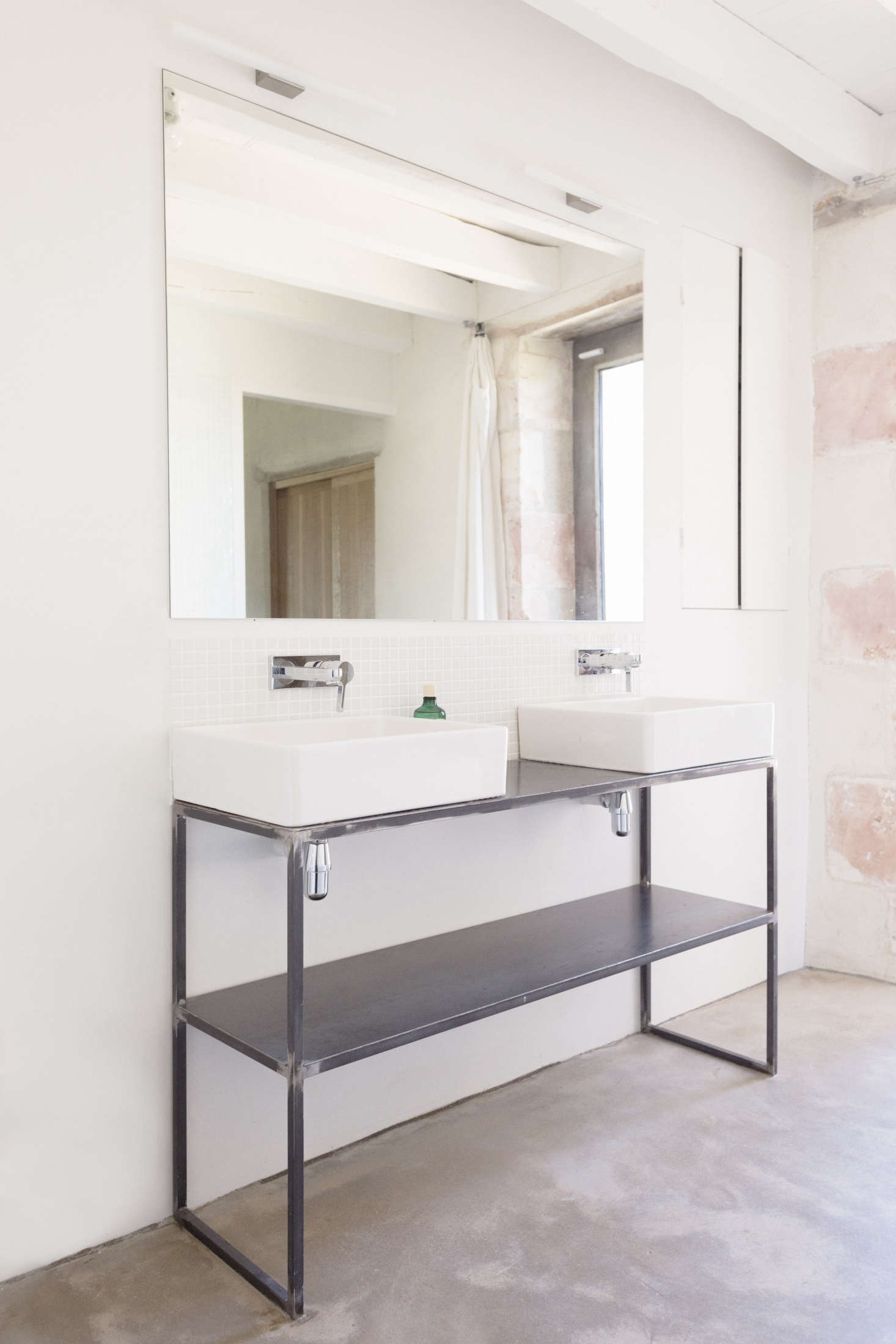 In the bathroom, double sinks stand on a welded-steel customvanity. The Metris Wall-Mounted Faucets are byHansgrohe;$227.50 from YLiving.