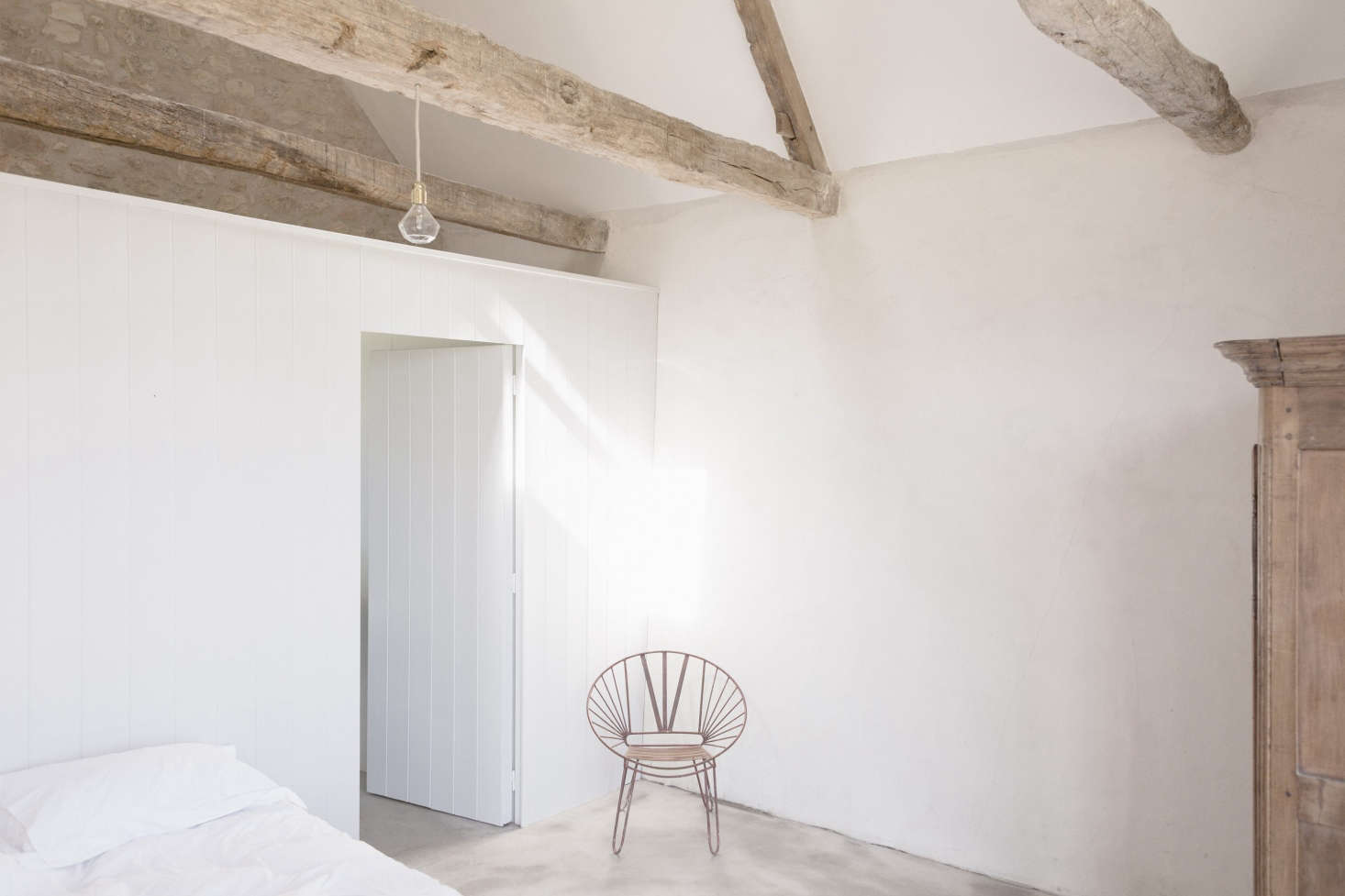 The exposed beams are celebrated in the sparsely decorated bedroom.