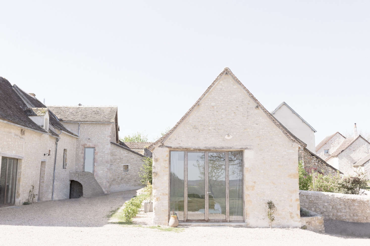 The farmhouse sits comfortably in the context of its surrounding village.