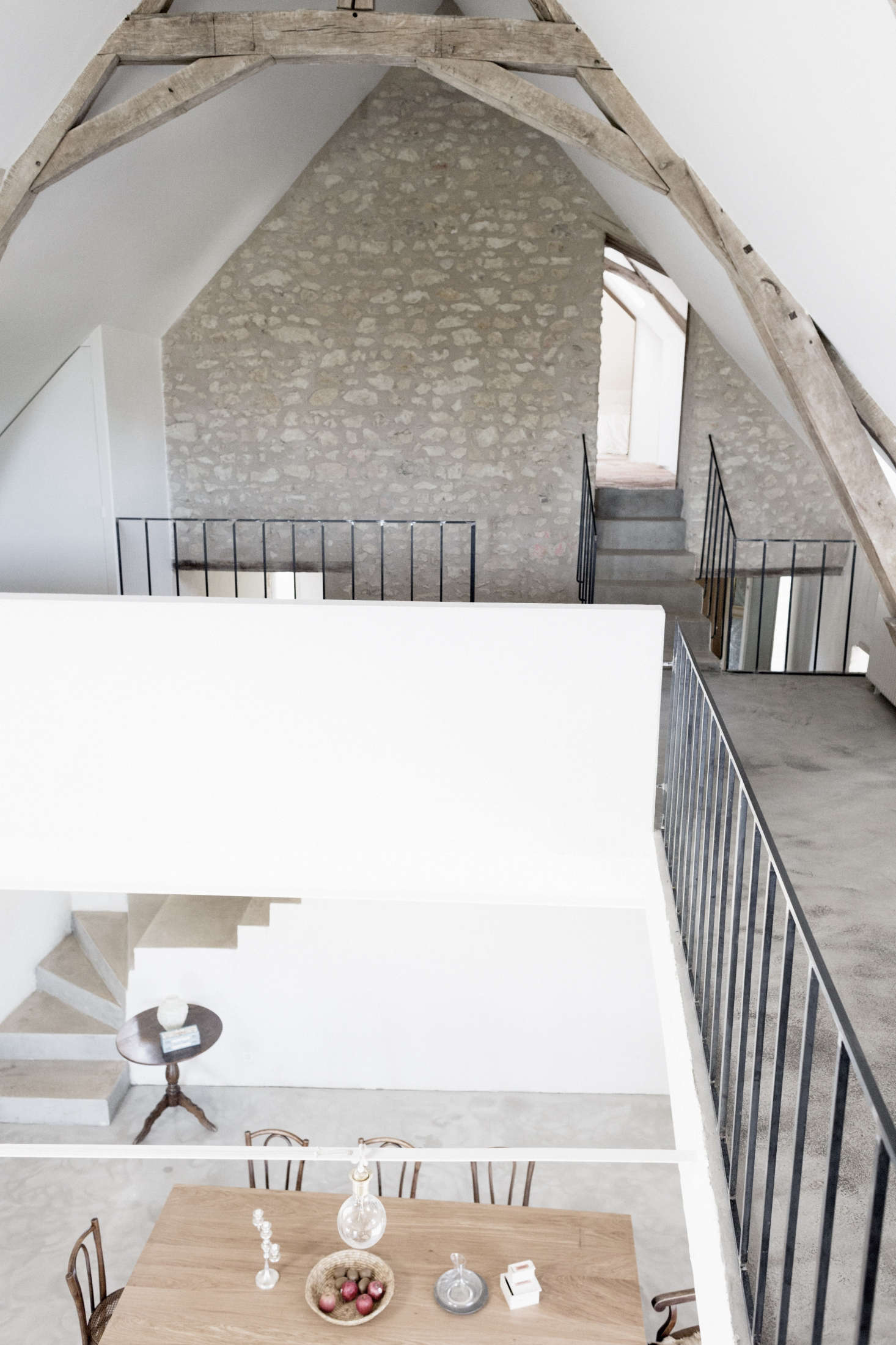 On the mezzanine, the simple, lightweight detailing of the metal rails contrasts with the heavy wood beams and stone walls of the original house.