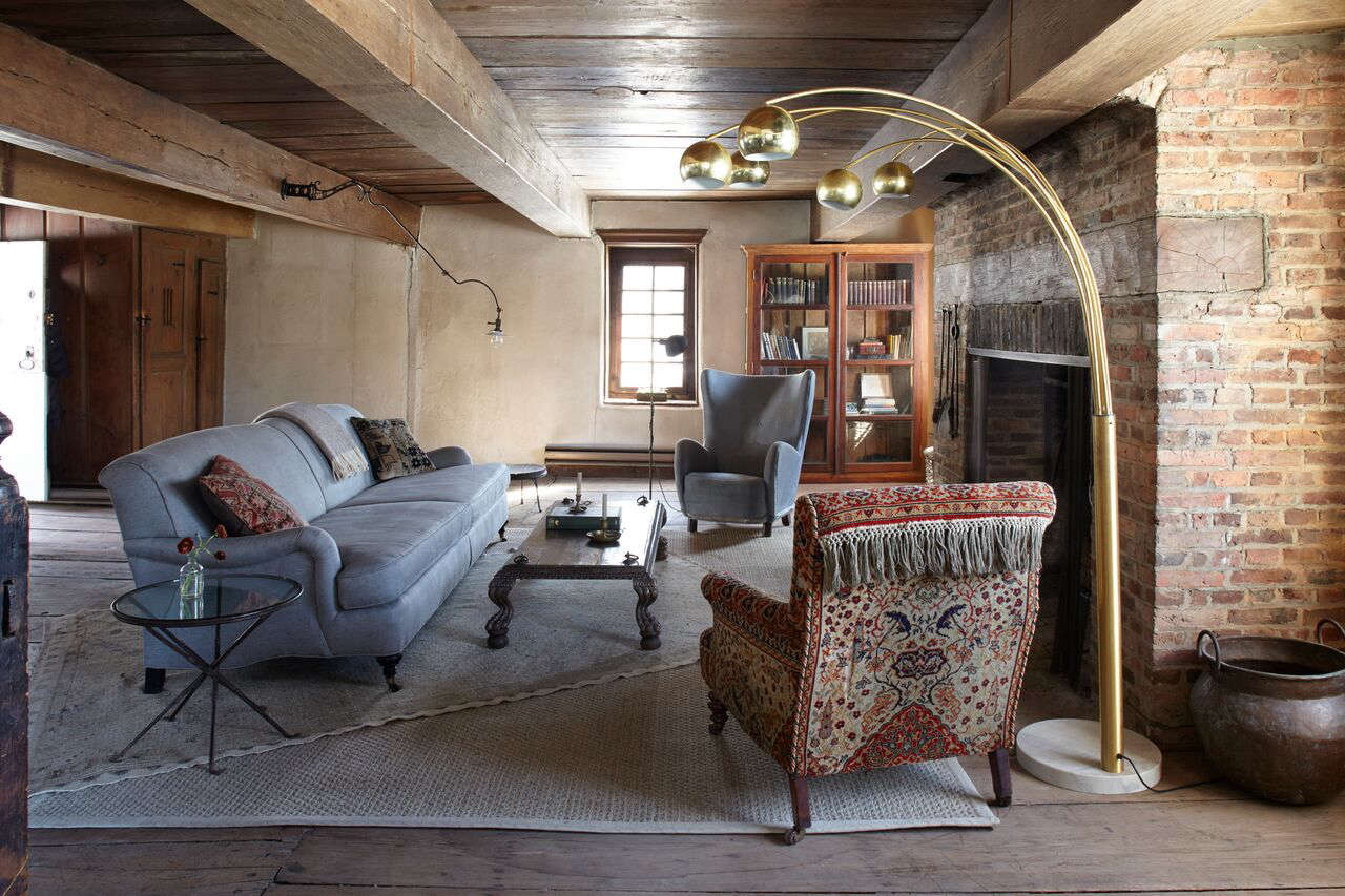 The English Roll Arm Sofa is from Restoration Hardware and the brass arc lamp with Italian marble base is from a Hudson antiques shop. The couple found the th century chair in Santa Barbara; the lamp mounted on the beam is a vintage Faries Fixtures dentists lamp from Luddite Antiques.