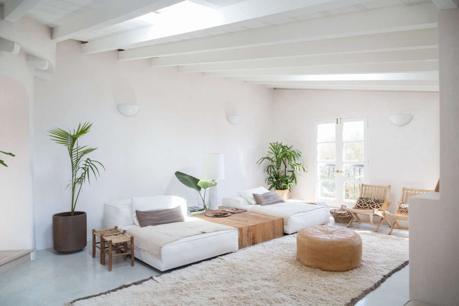 An airy living room channels laid-back LA livingwith low-slungwhite chaises (Living Divani modular sofas) and a custom white oak table. Golubovic found the midcentury woven chairs at a flea market in Chicago.