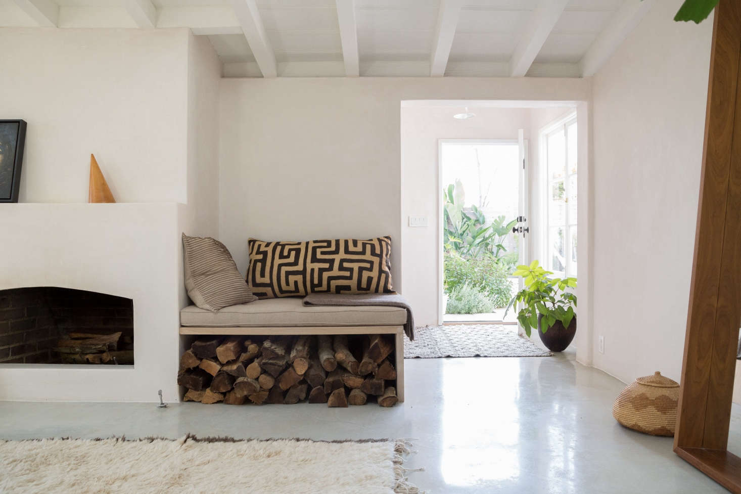 Golubovic updated the brick fireplace by creating a concrete front and then adding plaster over the top. A built-in bench alongside doubles as log storage.