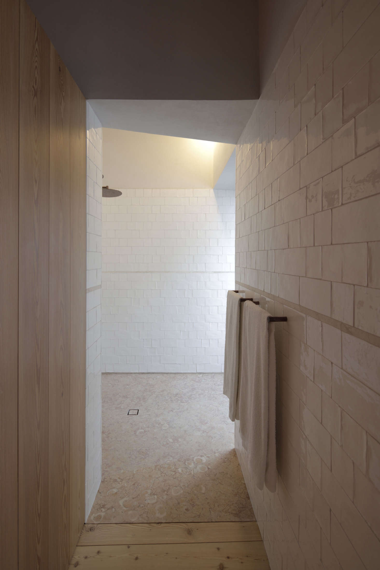 The shower drain is a simple rectangle cut in the limestone floor.