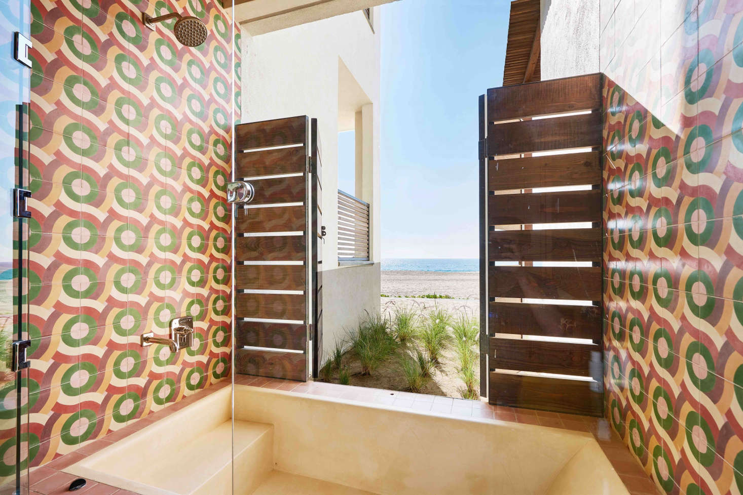 Shutters open this indoor/outdoor shower, lined in encaustic cement tile from Amethyst Artisan, to views of Punta Lobos beach. Fixtures are from Waterworks, and toiletries are by Malin & Goetz.