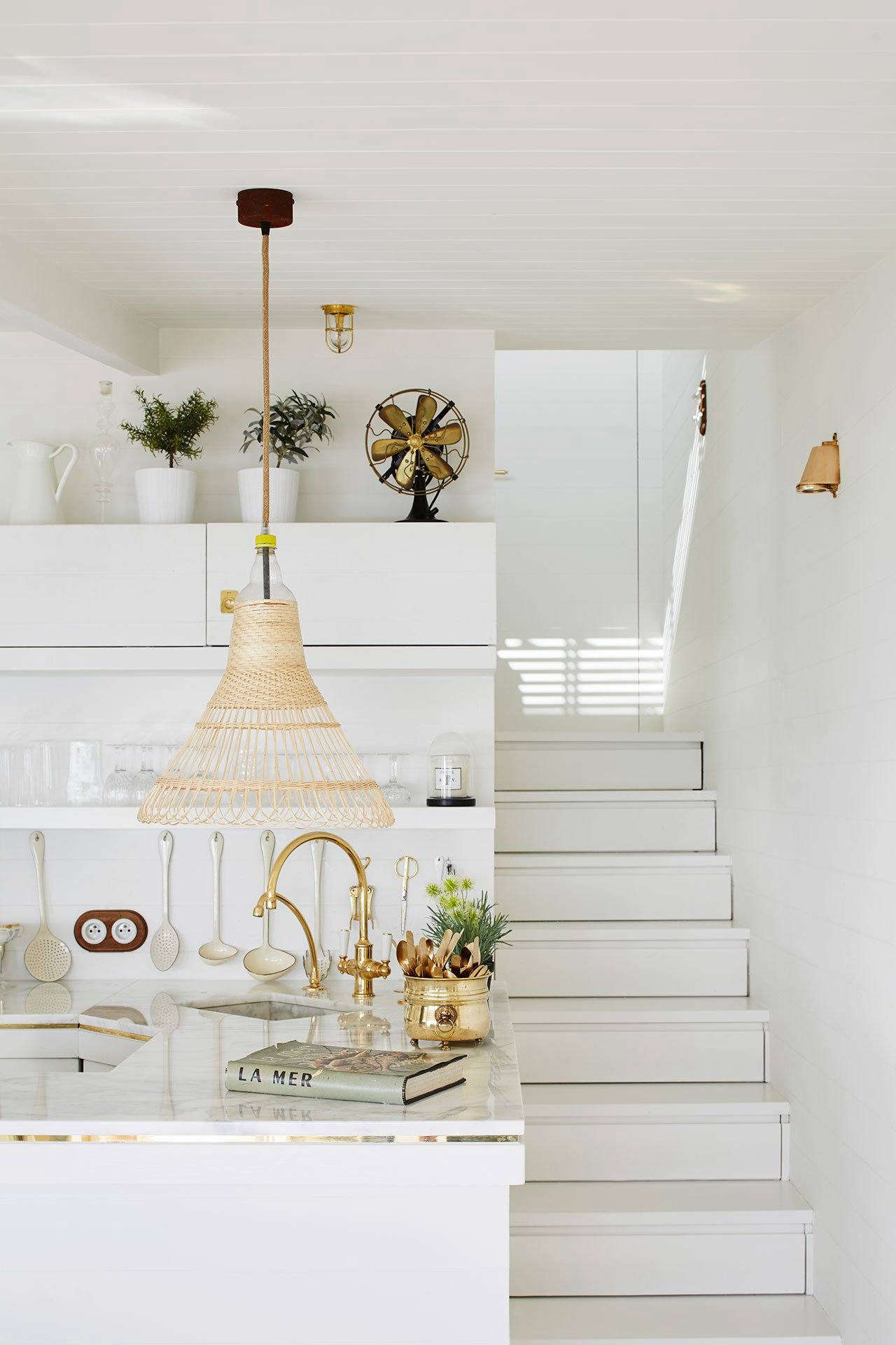 The marble-topped counter is edged with a band of brass and has a custom brass sink with a Lefroy Brooks gooseneck faucet. Note the drawers built into the stairs.