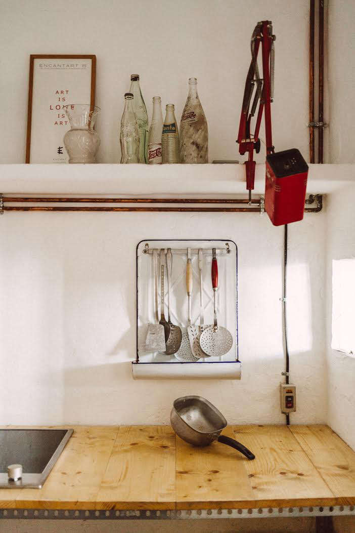 Quintana Partners travel for their finds: the kitchen's vintage enamelware utensil rack and clamp light came from a flea market in the South of France.