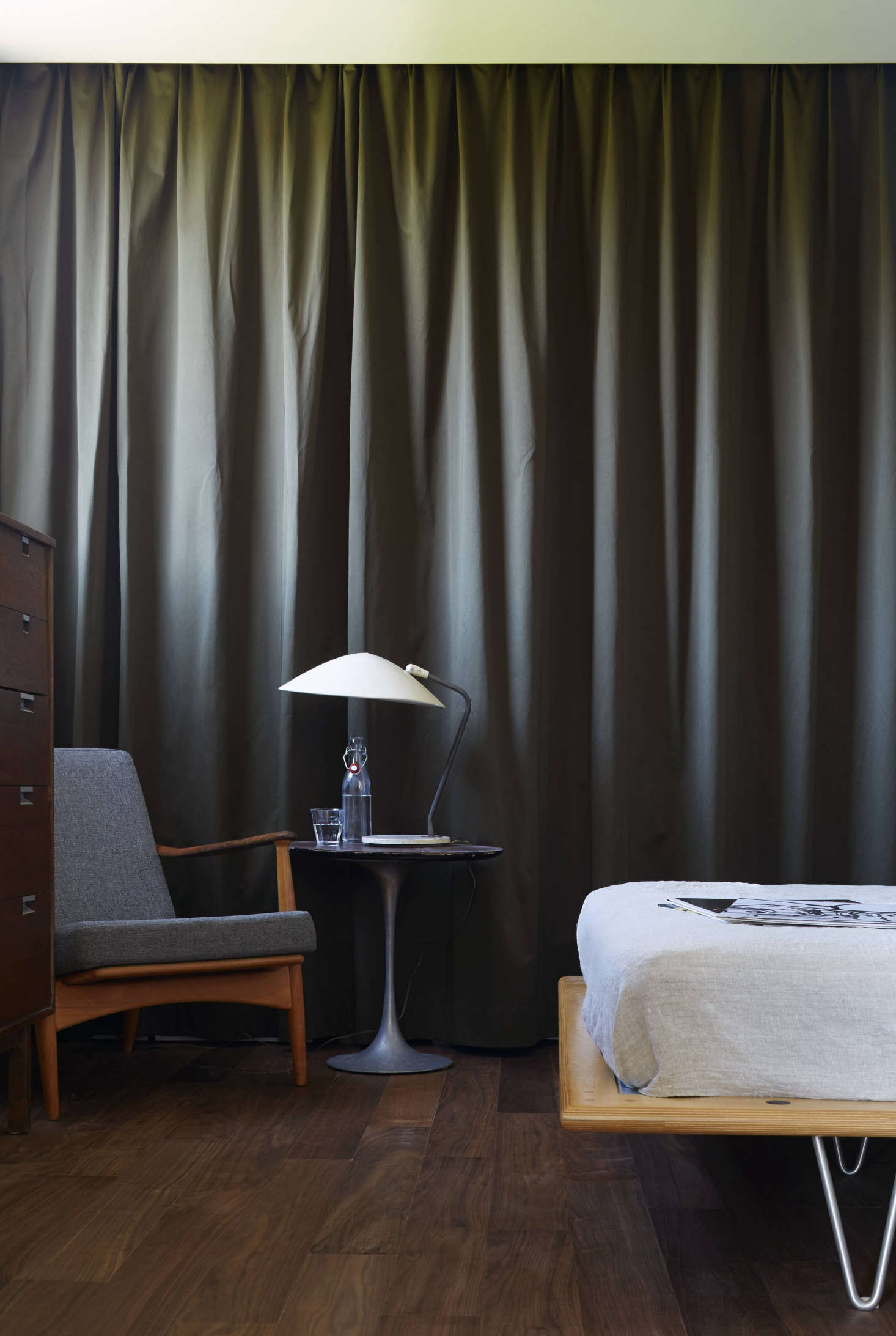 In the master bedroom, the closet is set off by olive-colored heavy cotton canvascurtains that hang from a ceiling track and conceal standard metal shelving. &#8