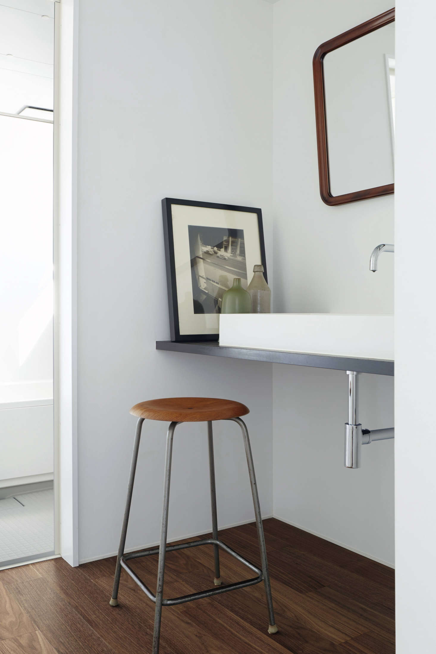In the family bath, a stained Douglas fir shelf supports a simple sink and serves as a place to prop art. The designers used an affordable off-the-shelf Japanese unit system in the inner bathroom.