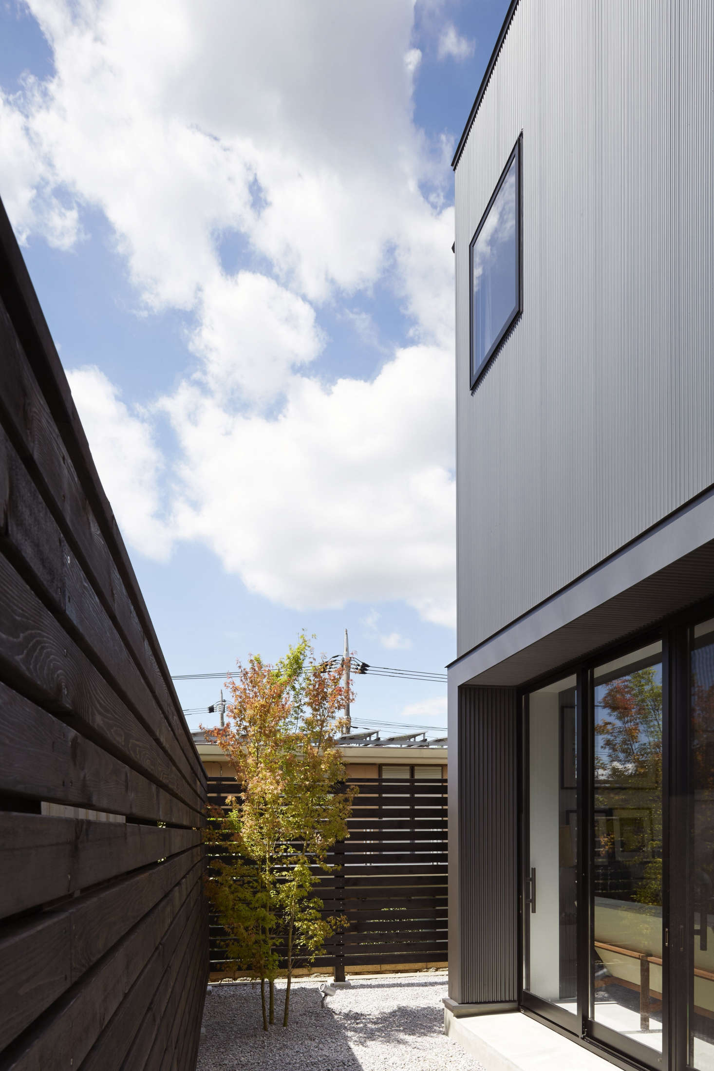 The gravel-lined courtyard serves as a buffer between the house and its next-door neighbor.